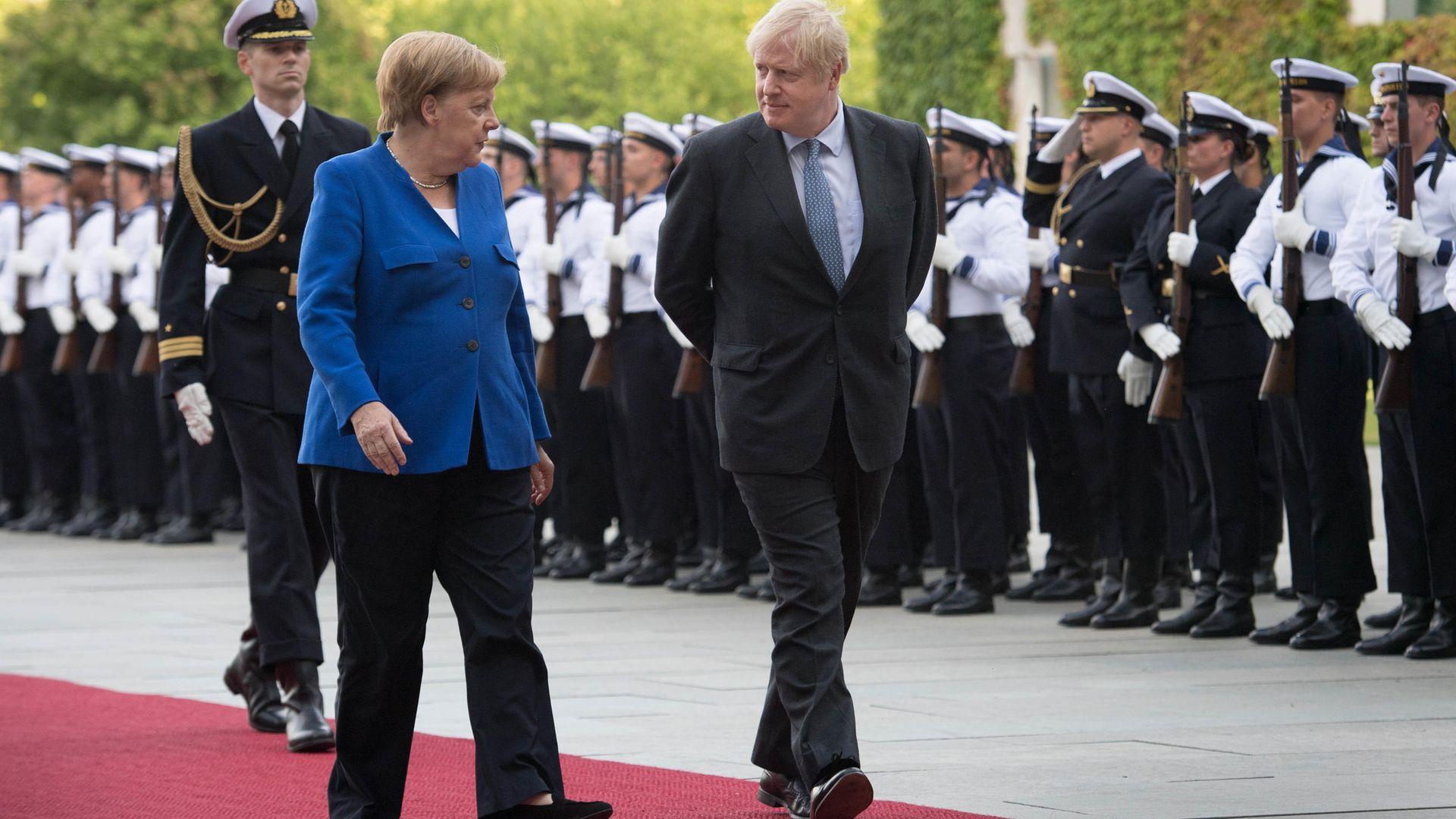 Prime Minister Boris Johnson walks with German Chancellor Angela Merkel in Berlin - Credit: PA