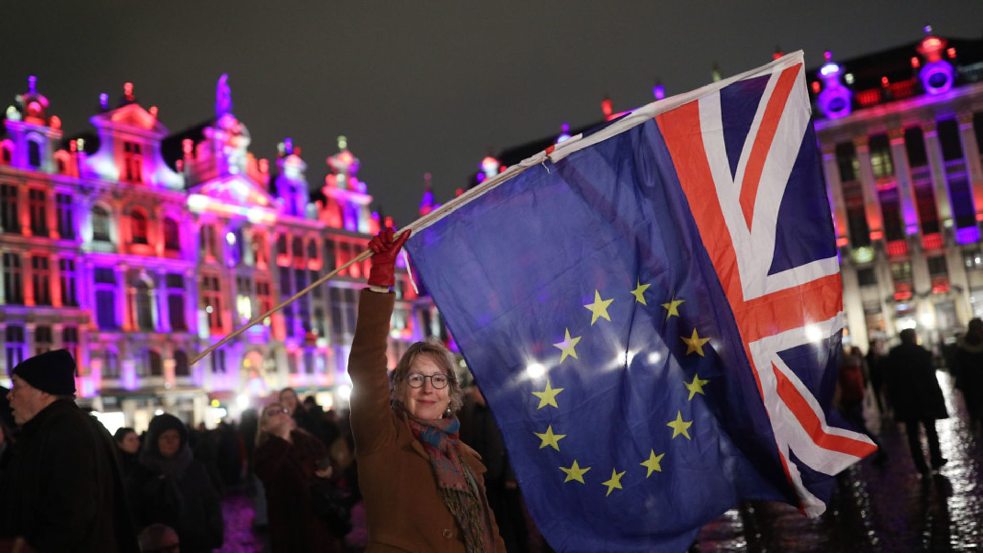 Deirdre Thomas, a resident of Belguim, waving an EU flag and a Union jack in Grand Place in Brussels, Belgium. - Credit: PA