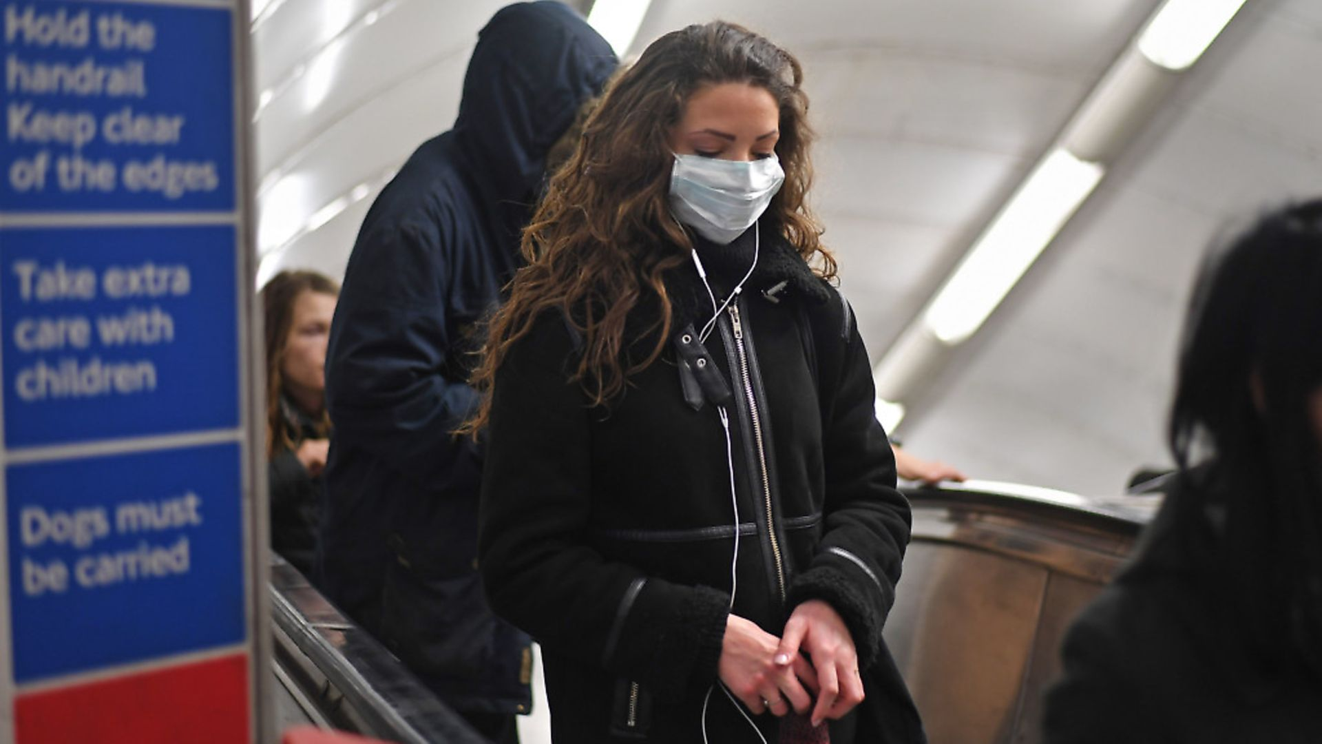 A woman at Green Park station on the London Underground tube network wearing a protective facemask. Photograph: Kirsty O'Connor/PA Wire. - Credit: PA