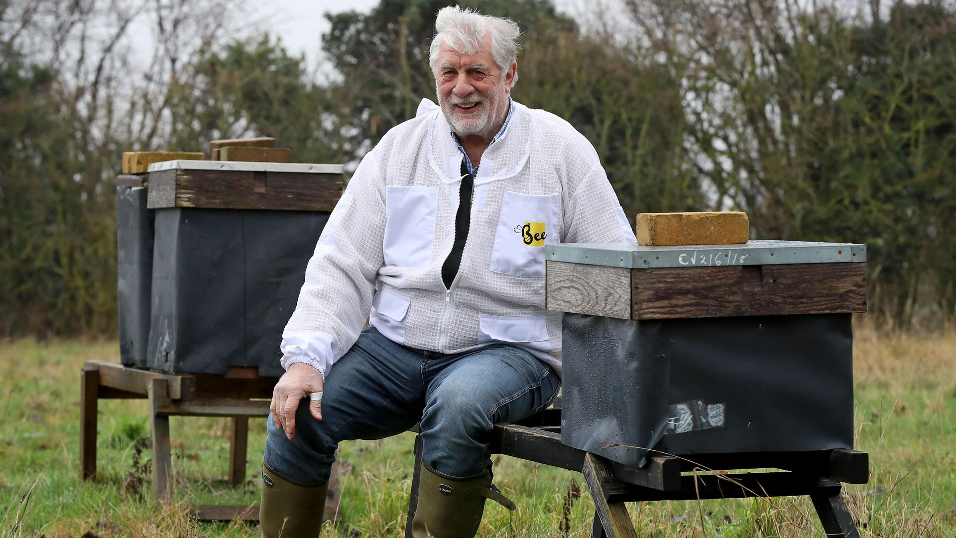 Beekeeper Patrick Murfet sits amongst some of his hives in an orchard near Canterbury in Kent, as he is told the 15 million bees he wants to bring into the UK for next spring may be seized and destroyed if he does - Credit: PA