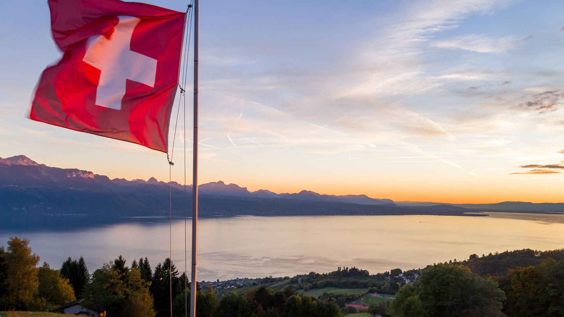 Flying the flag for languages.... a Swiss flag is seen floating at sunset above Lake Geneva - Credit: AFP via Getty Images