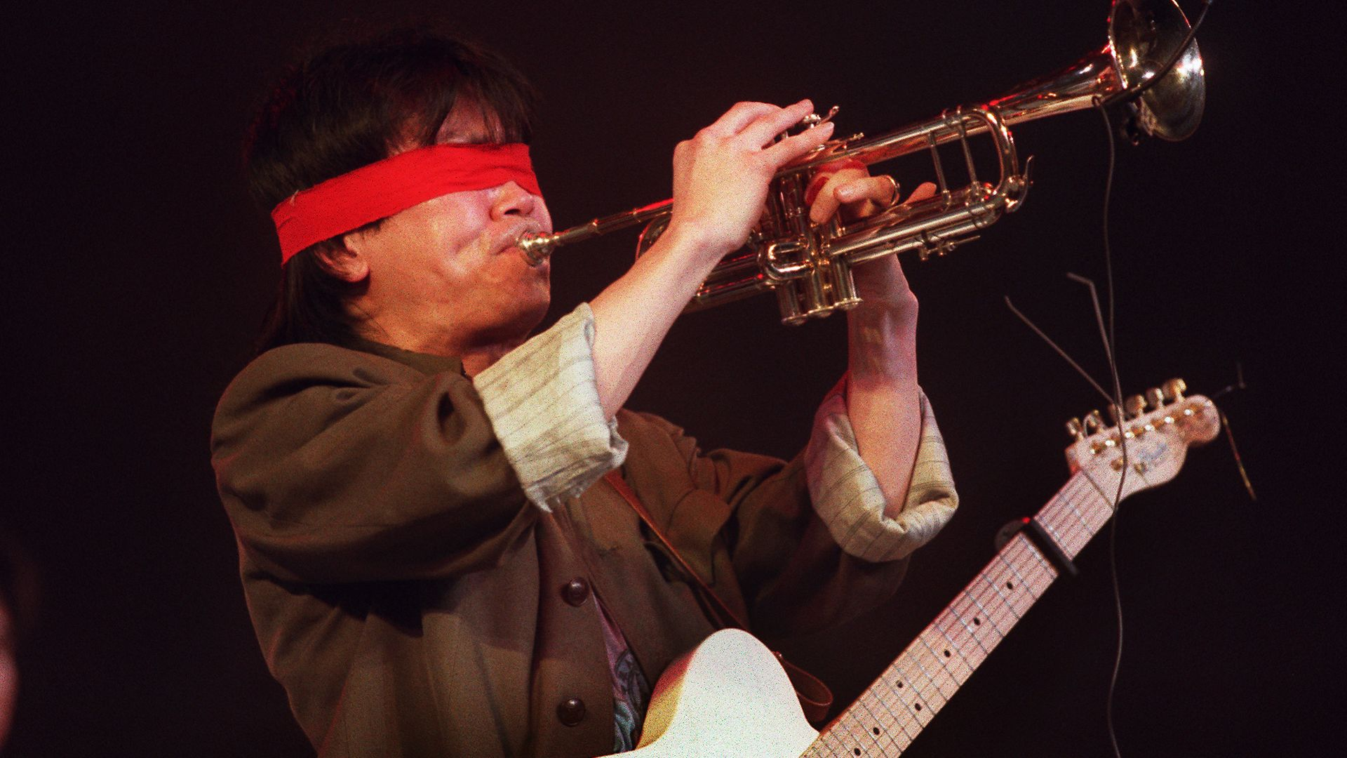 A blindfolded Cui Jian performs in Nanjing, in 1992. It was the rocker's first officially sanctioned appearance in two years. His politically-charged lyrics are frowned upon by authorities - Credit: AFP via Getty Images