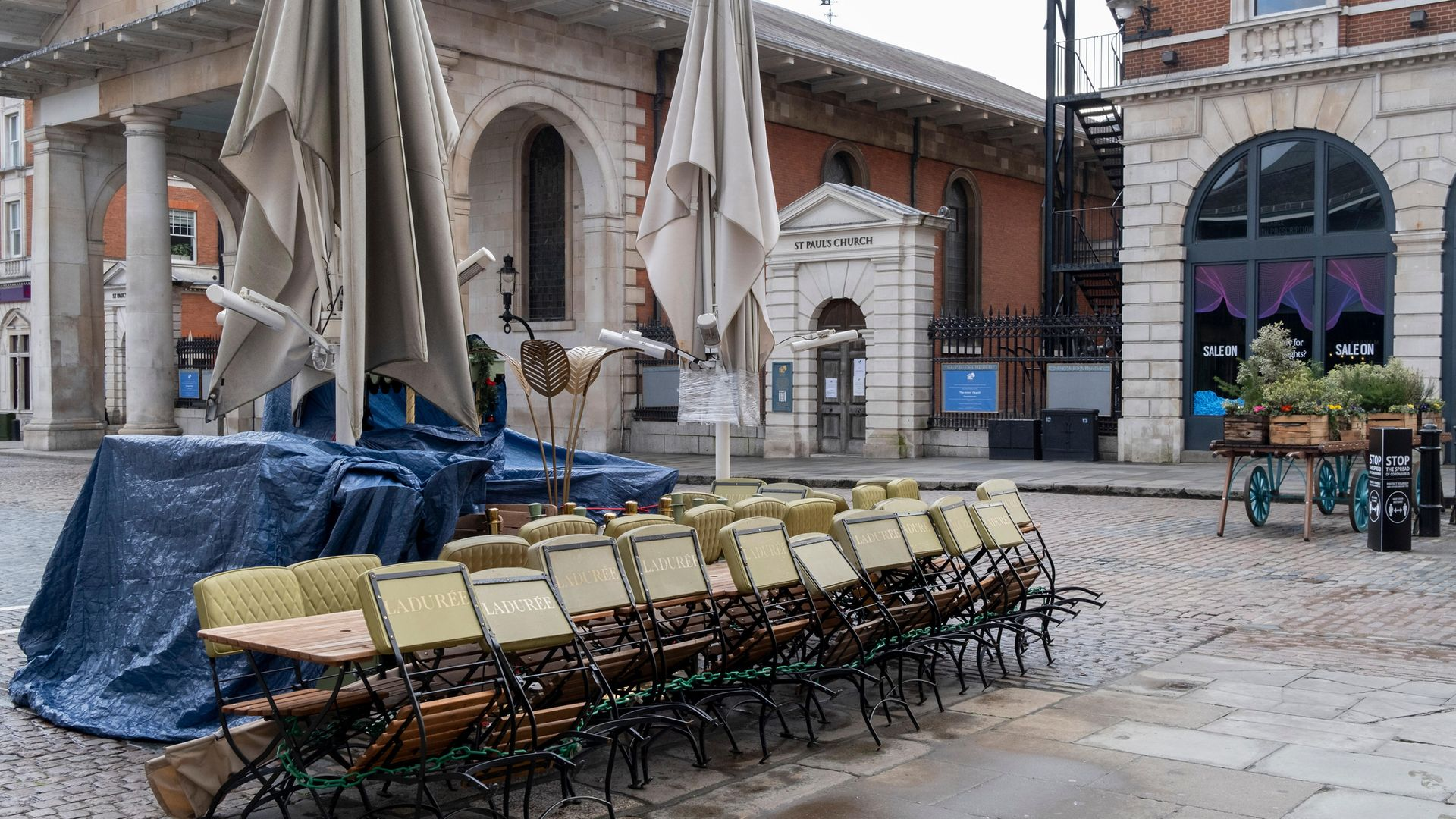 Tables and chairs from a closed restaurant business are stacked and tied together in the Covent Garden Piazza - Credit: In Pictures via Getty Images