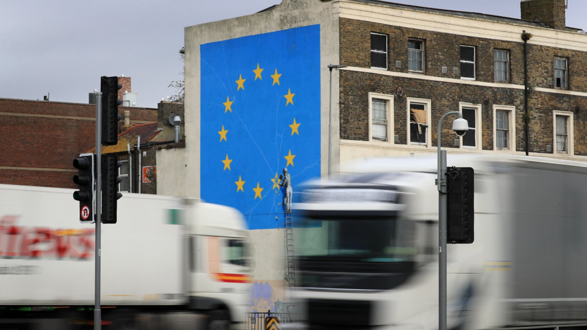Lorries pass the Brexit-inspired mural by artist Banksy in Dover - Credit: PA Wire/PA Images