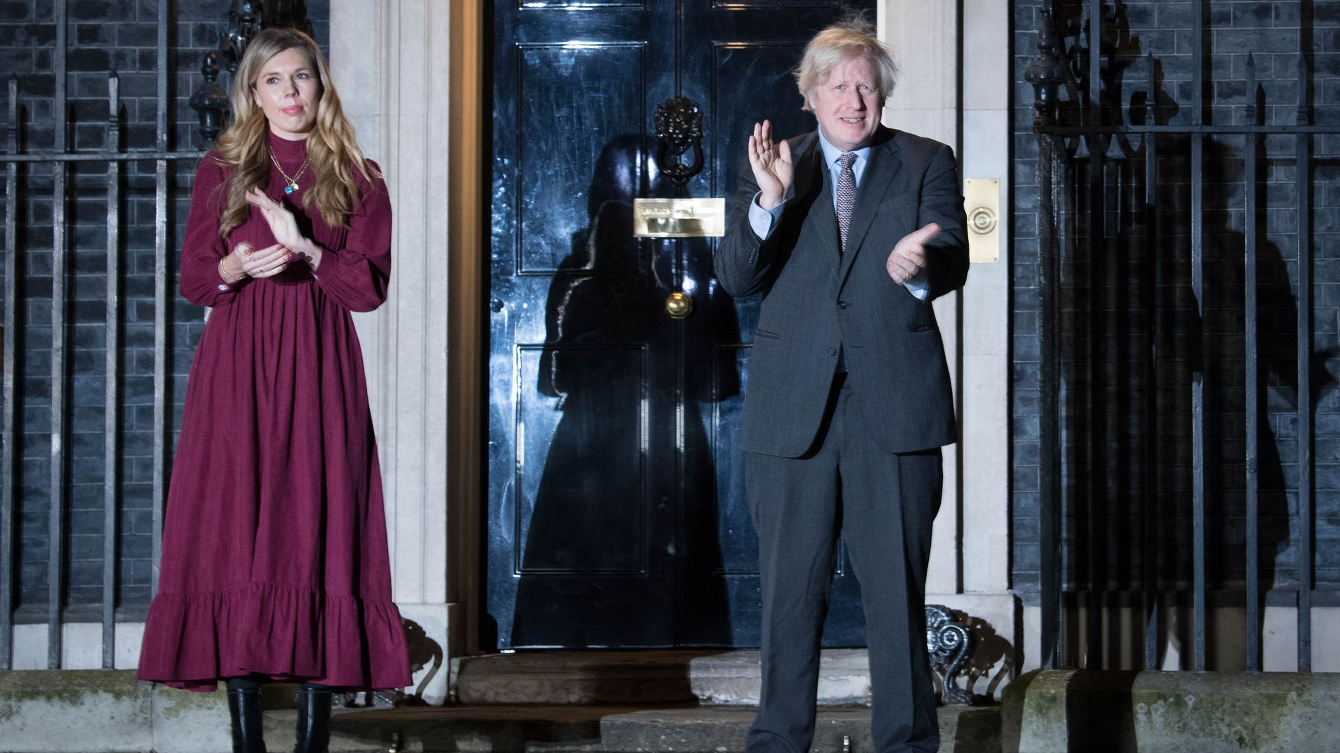 Prime Minister Boris Johnson and his partner Carrie Symonds stand outside 10 Downing Street to join in with a nationwide clap - Credit: PA