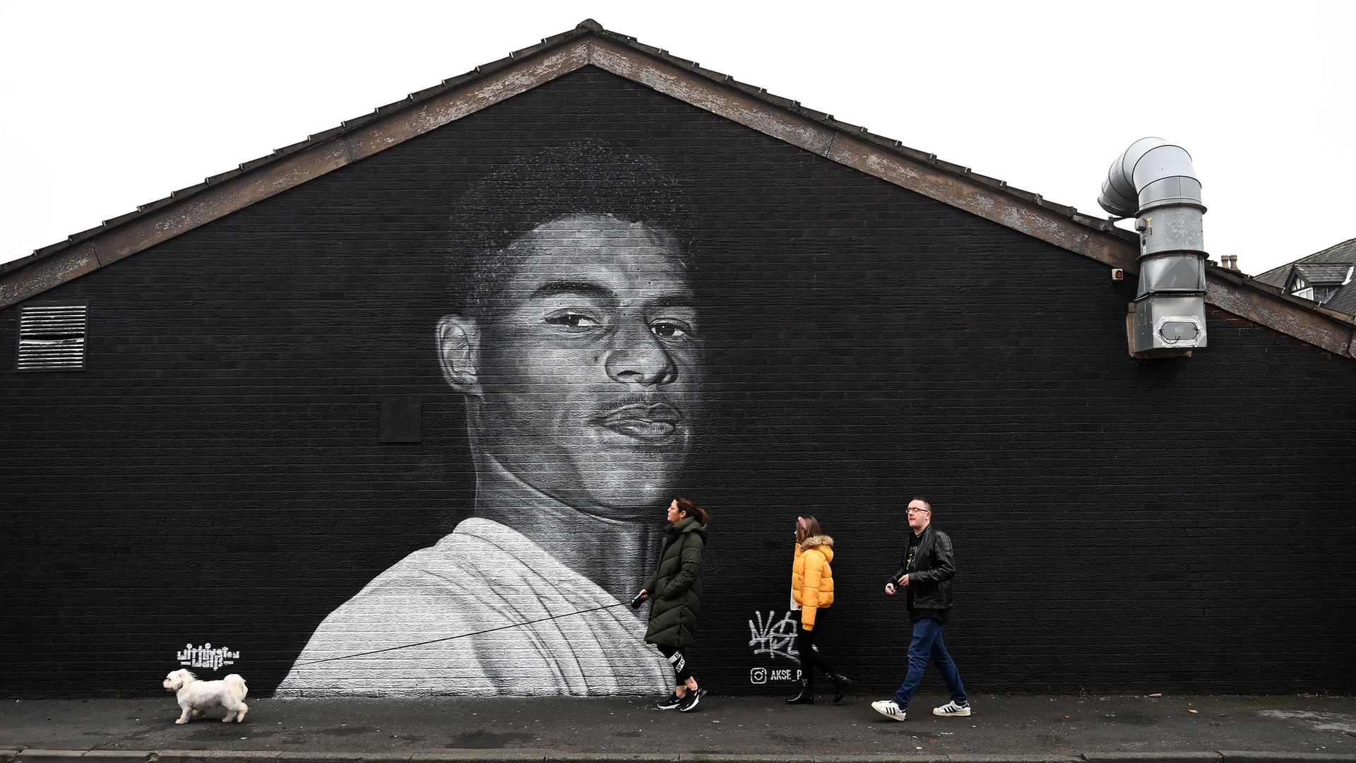 A mural by artist Akse P19 of Marcus Rashford on the side of a building in Withington, Manchester - Credit: AFP via Getty Images