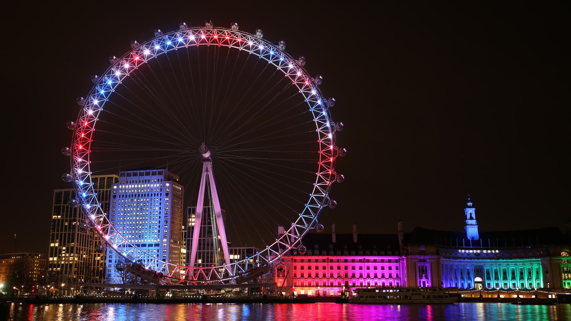 The London Eye and buildings along the South Bank are lit up with the colours of the Union flag - Credit: PA