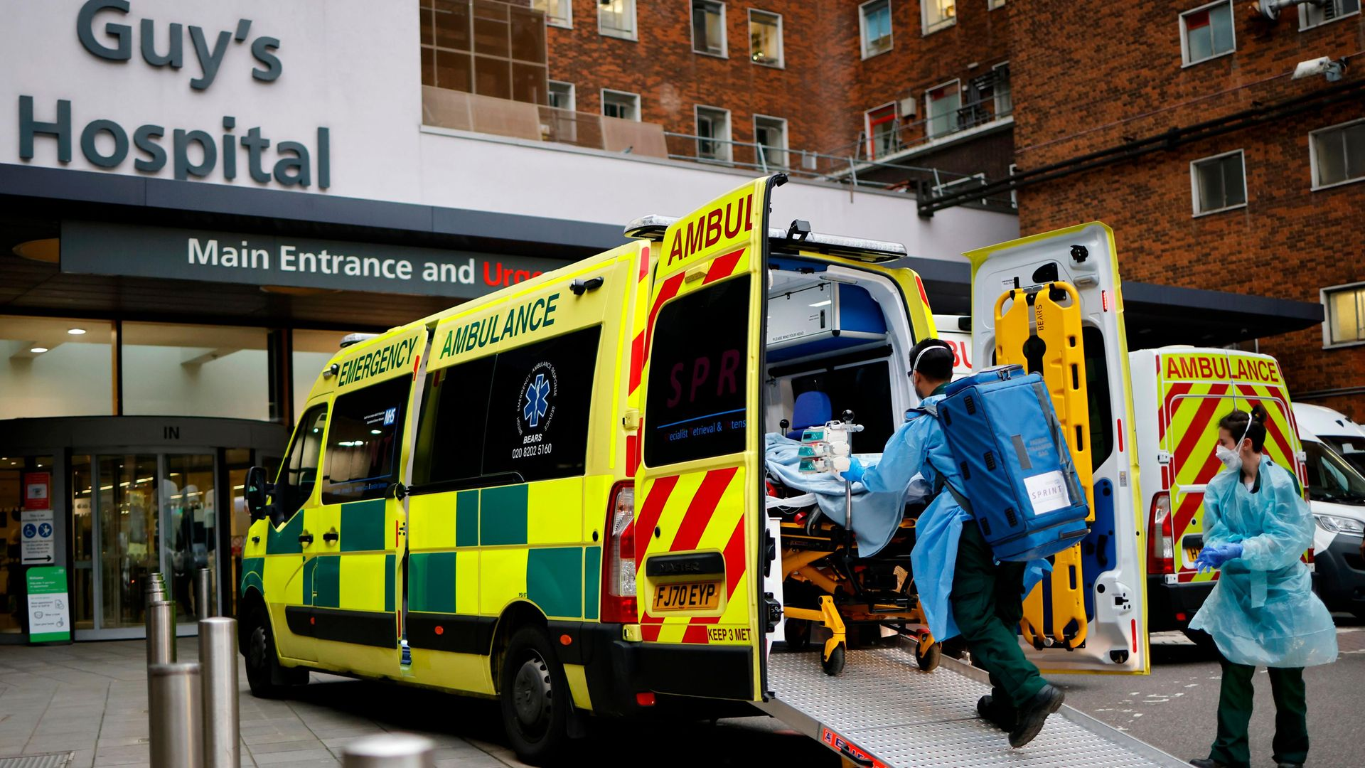 A patient on a gurney is taken from an ambulance parked outside Guy's Hospital in London - Credit: AFP via Getty Images