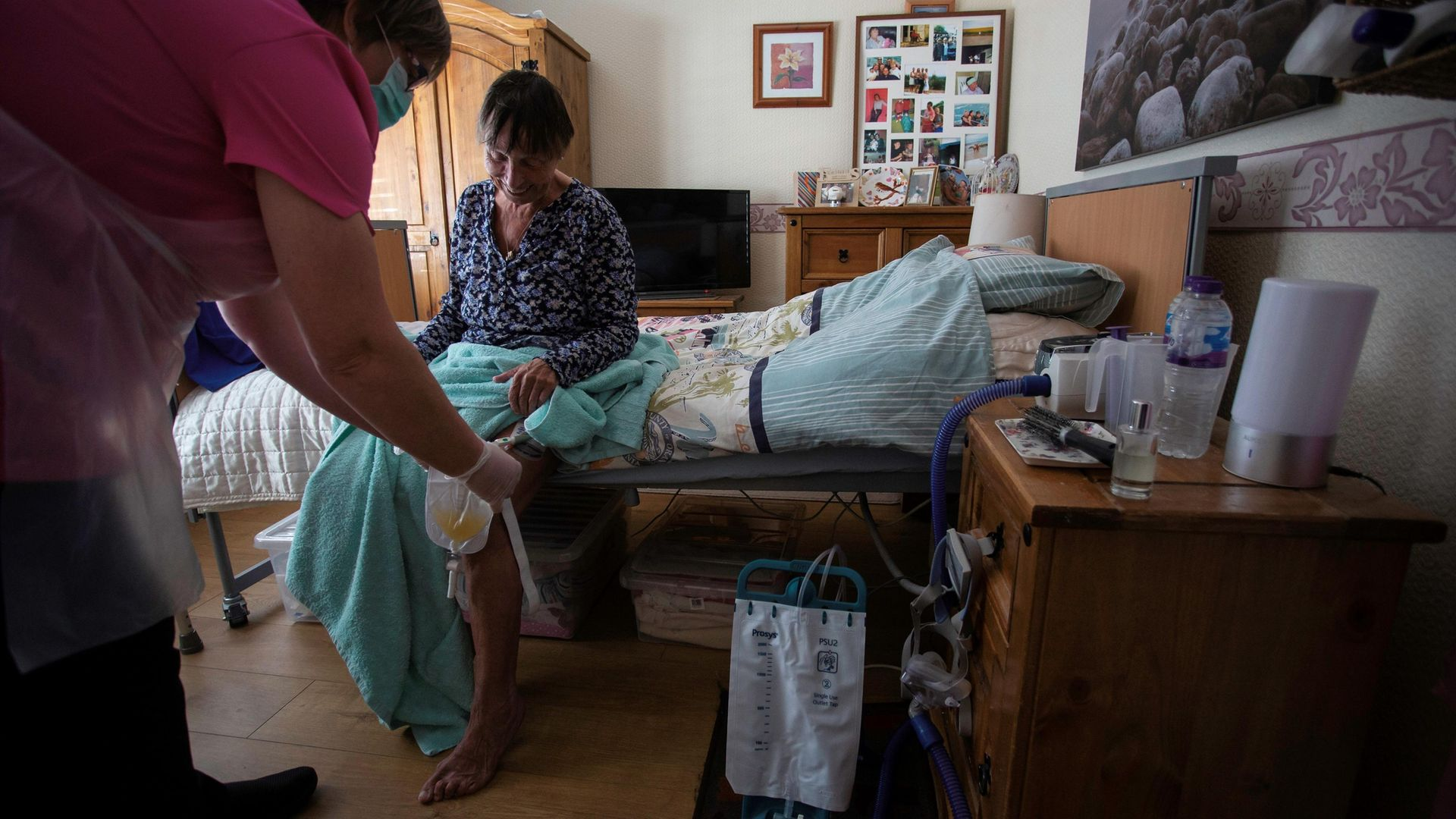 Dawn, a carer, tends to her client Tina during a home visit in Scunthorpe - Credit: AFP via Getty Images