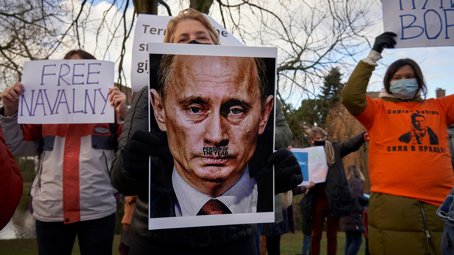 Demonstrators hold up banners in front of the Russian embassy in The Hague, Netherlands - Credit: Getty Images