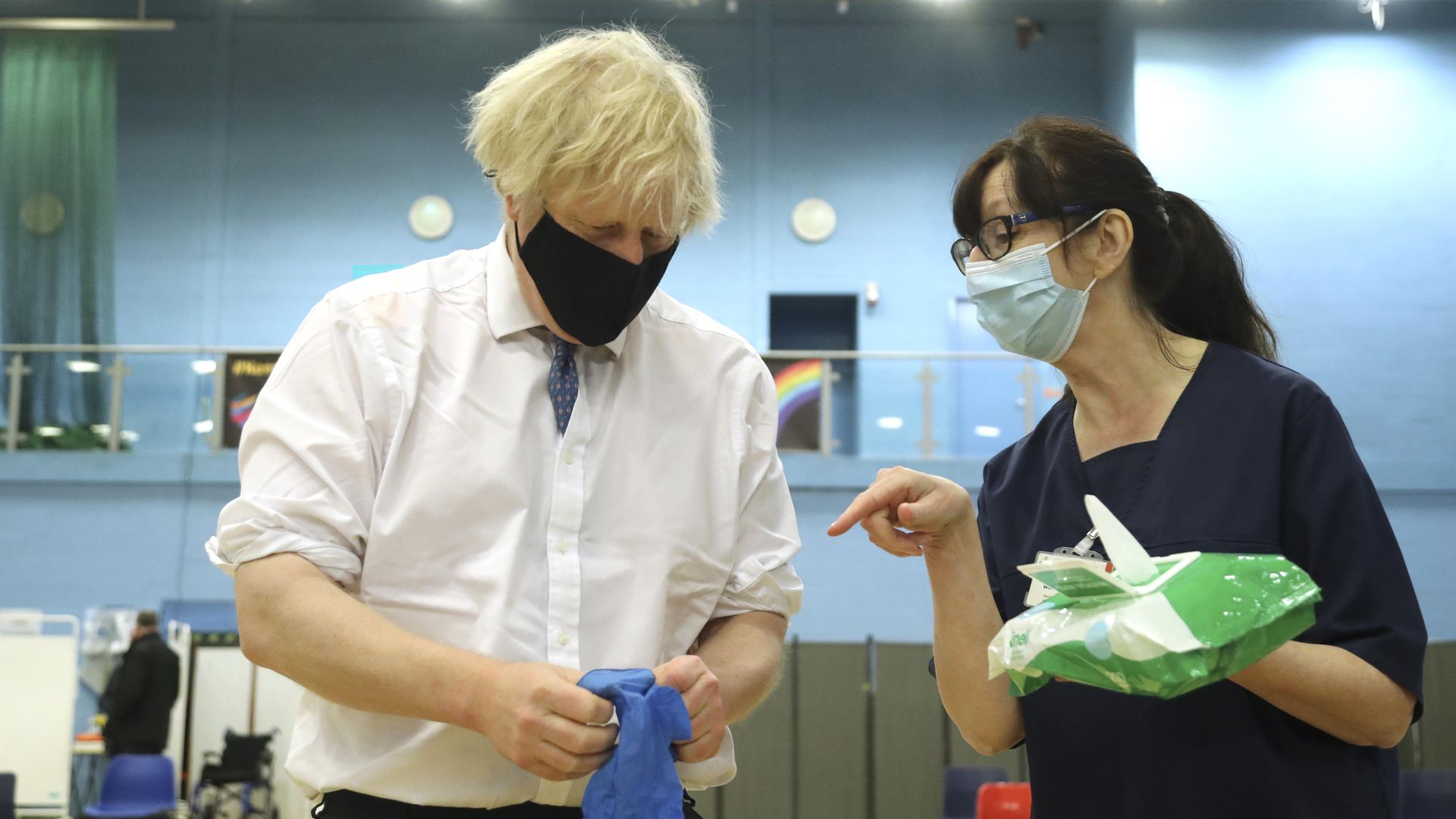 Prime minister Boris Johnson speaks with health worker Wendy Warren as he puts on a pair of medical gloves during a visit to a vaccination centre at Cwmbran Stadium in Cwmbran, south Wales - Credit: PA
