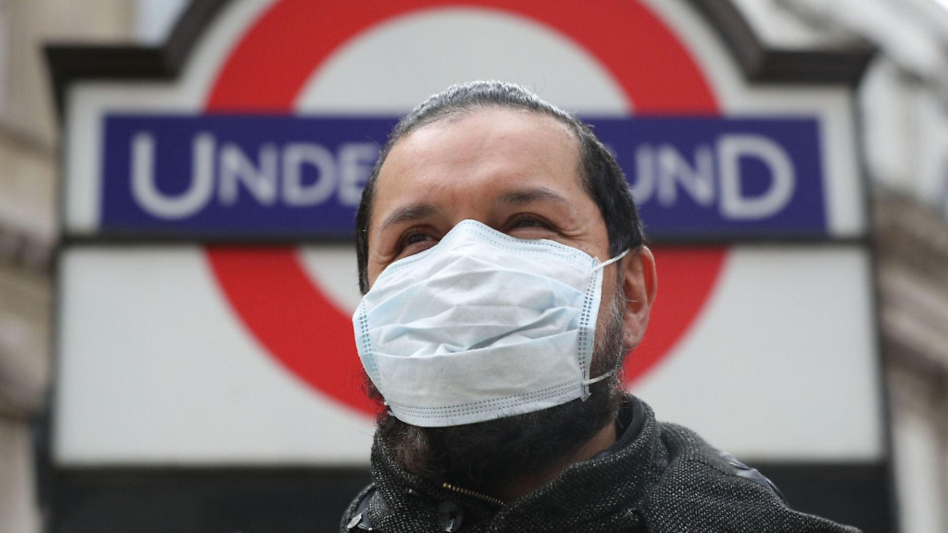 A person wearing a face mask in front of an underground sign in London. Photograph: Jonathan Brady/PA Wire. - Credit: PA