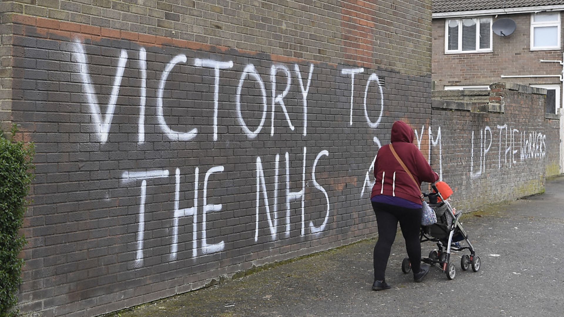 A woman walks past a message of support for the NHS in Londonderry, as the UK continues in lockdown to help curb the spread of the coronavirus. PA Photo. Picture date: Tuesday March 31, 2020. A total of 1,408 patients have died after testing positive for coronavirus in the UK as of 5pm on Sunday. See PA story HEALTH Coronavirus. Photo credit should read: Michael Cooper/PA Wire - Credit: PA