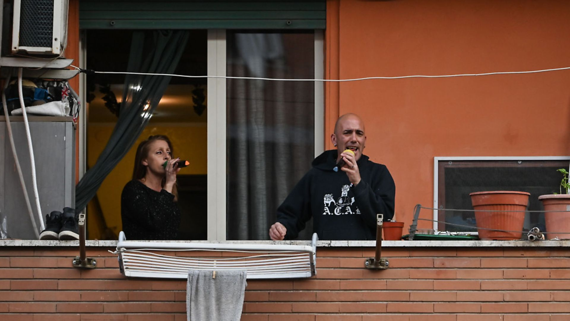 """Italians join the flash mob call to perform """"Una canzone per l'Italia"""" in the Magliana district of Rome, March 15. Picture: Getty Images - Credit: AFP via Getty Images"""