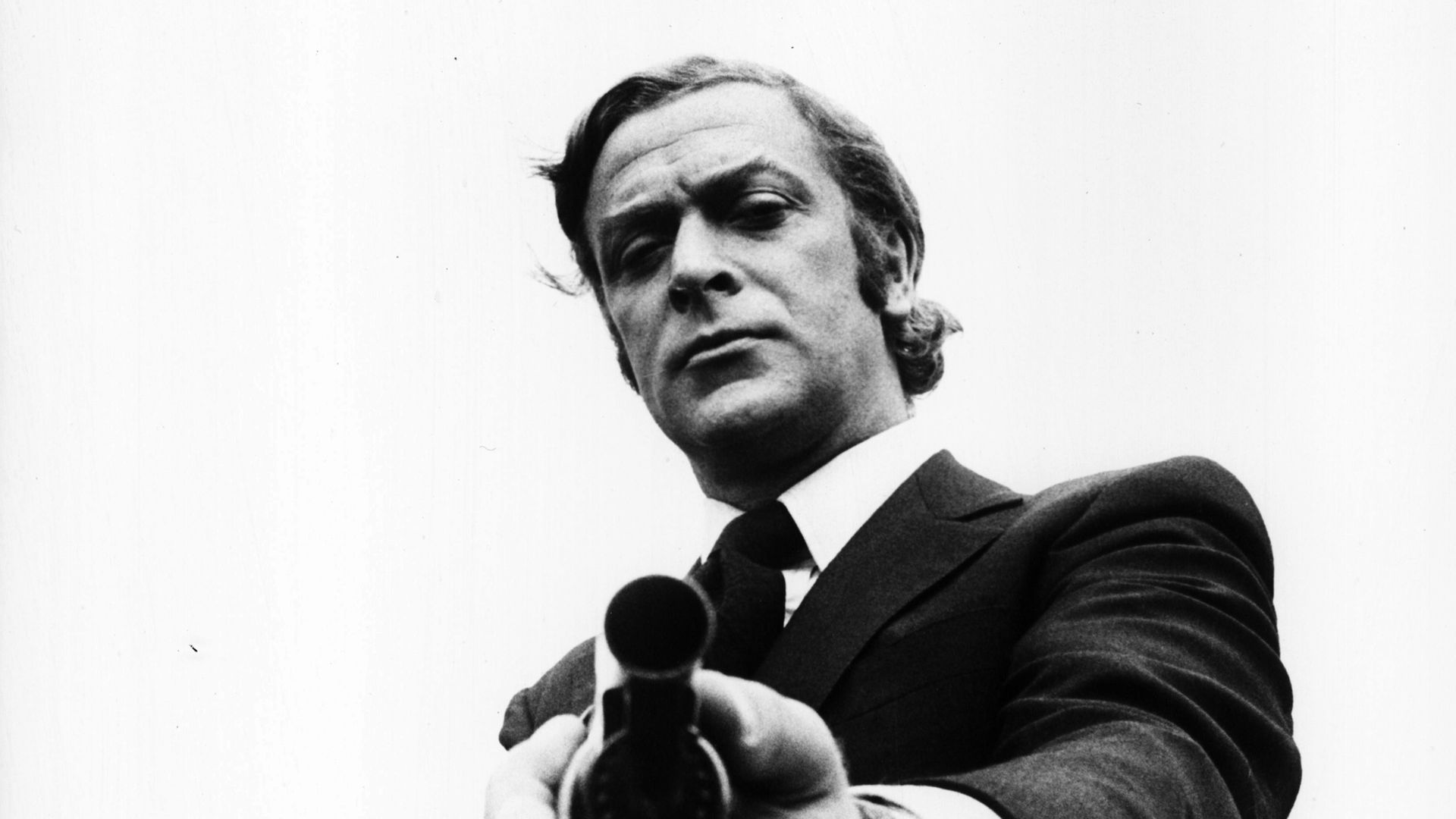 Portrait of actor Michael Caine pointing a gun towards the camera, as he appears in the film 'Get Carter', 1971. (Photo by Stanley Bielecki Movie Collection/Getty Images) - Credit: Getty Images