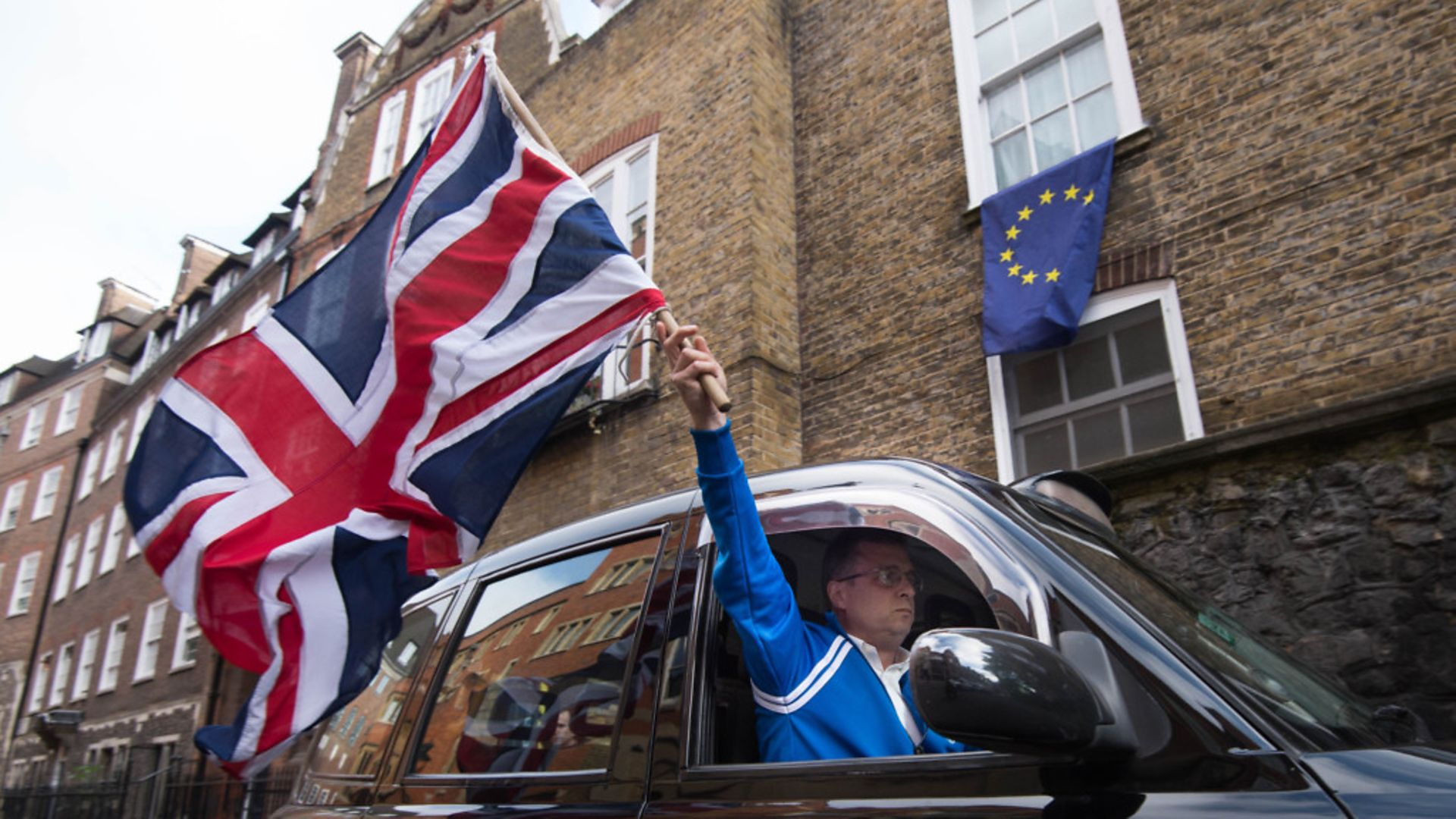 A London taxi driver waves a Union Jack flag in Westminster after the Brexit vote - Credit: PA