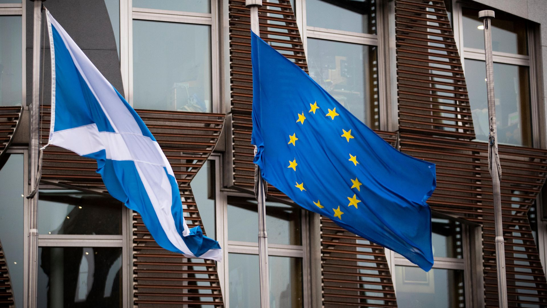 The Saltire and EU flag fly outside the Scottish Parliament in Edinburgh - Credit: PA