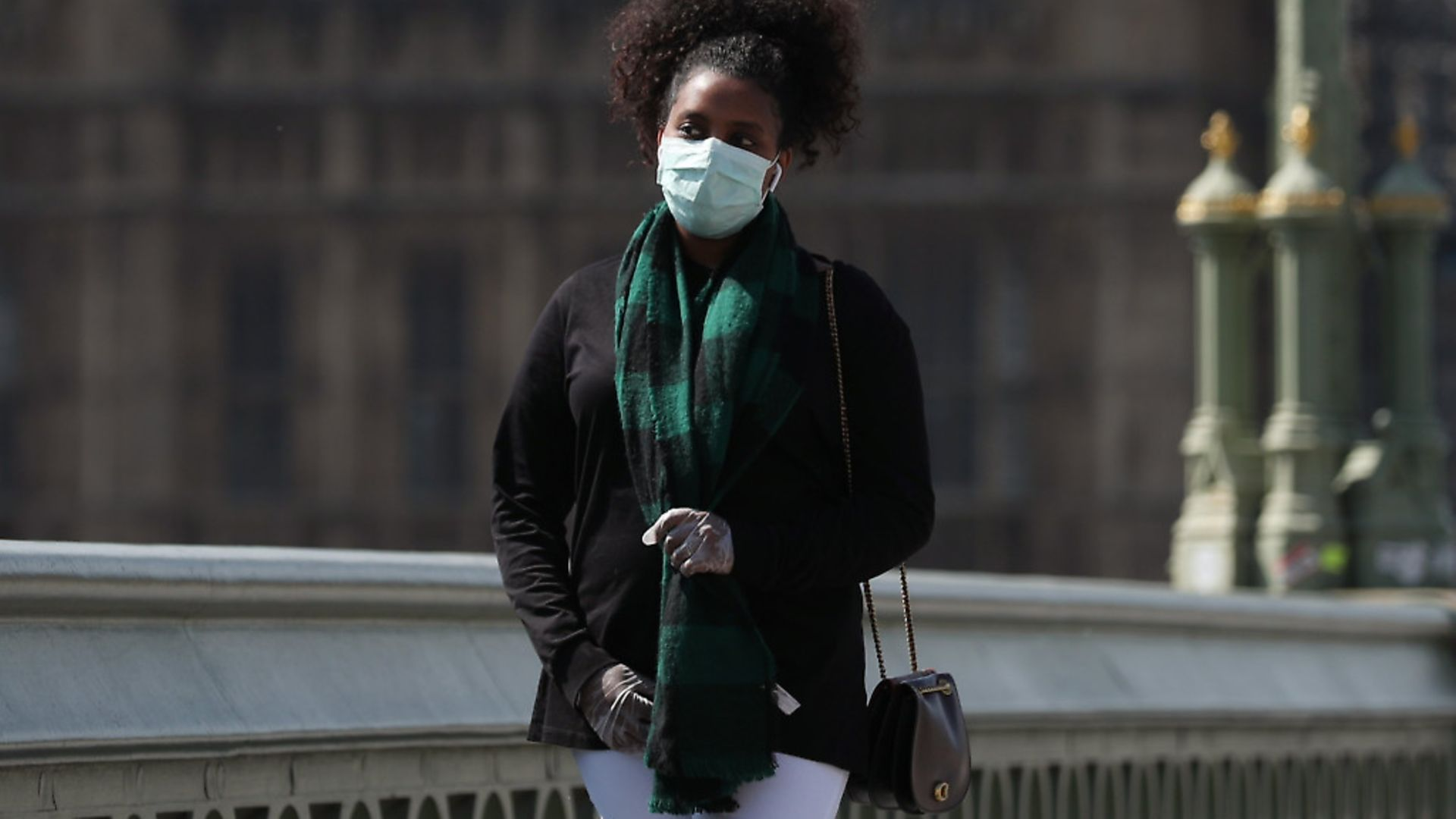 A passer-by wears a face mask on Westminster Bridge in London as the UK continues in lockdown to help curb the spread of the coronavirus. Photograph: Yui Mok/PA. - Credit: PA