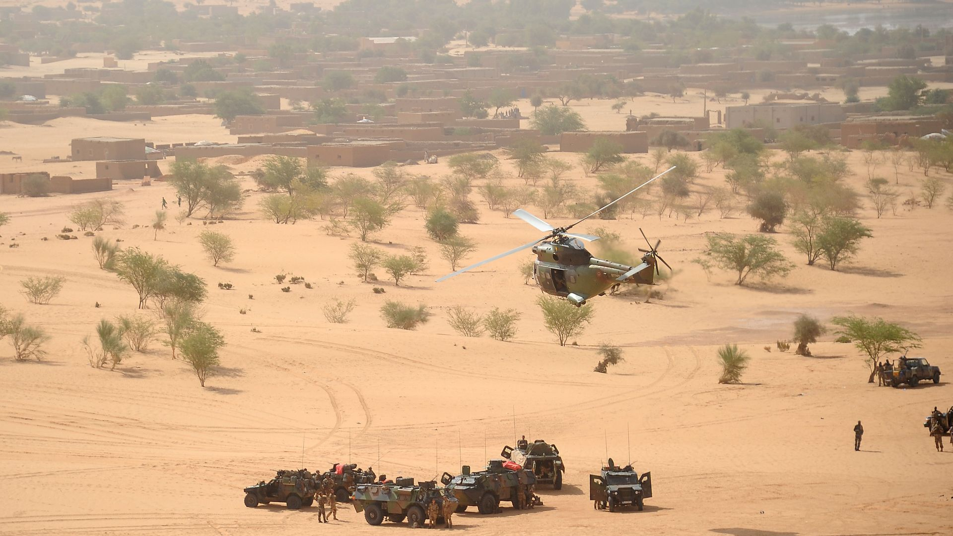 A Puma helicopter flies above French military vehicles near Bourem, northern Mali - Credit: AFP via Getty Images