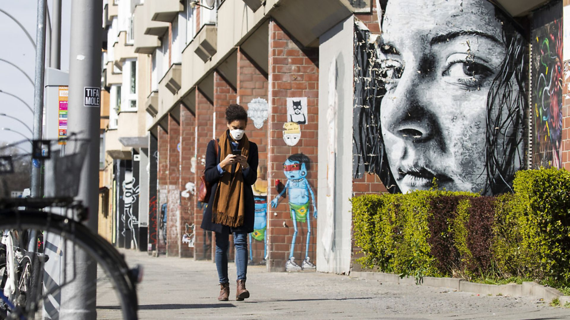 A young woman wearing a protective mask looks at her smartphone while passing by a grafitti representing a watching woman in Berlin, Germany. Picture: Emmanuele Contini/NurPhoto via Getty Images - Credit: NurPhoto via Getty Images