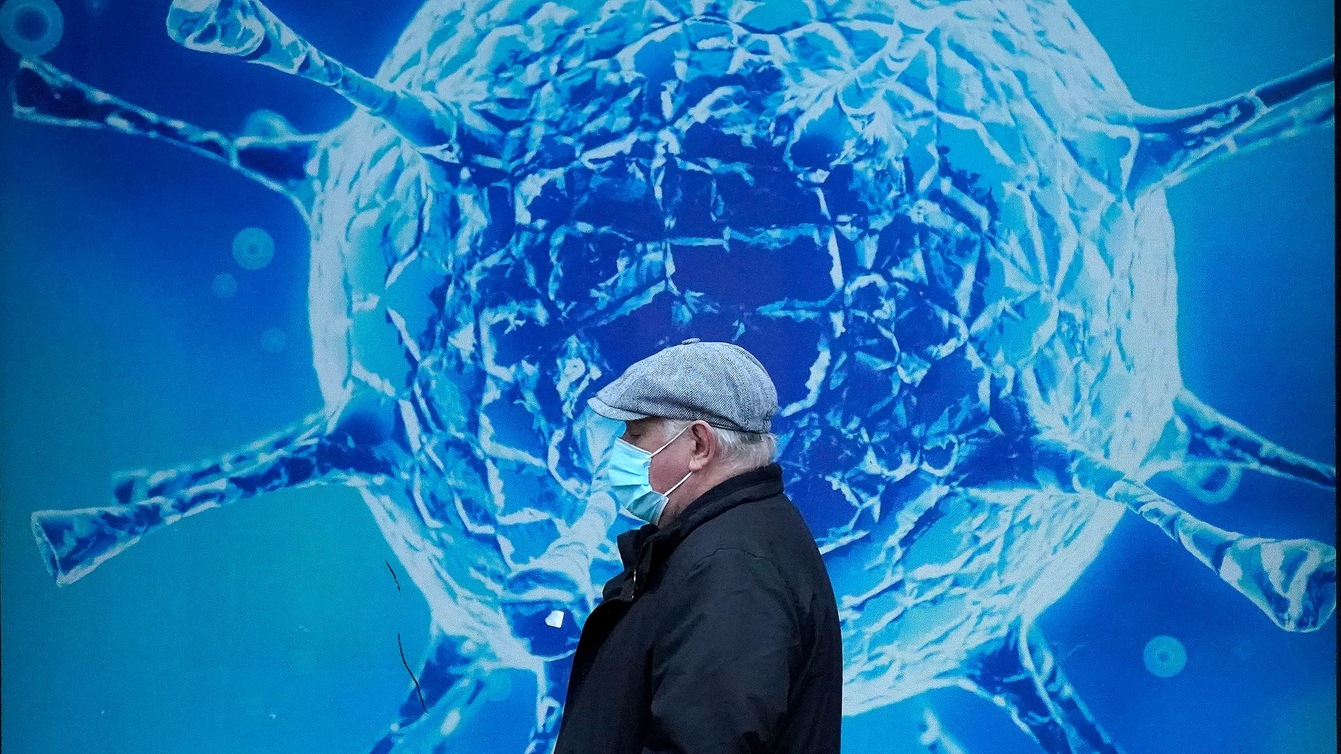A man wearing a protective face mask walks past an illustration of a virus outside in Oldham - Credit: Getty Images