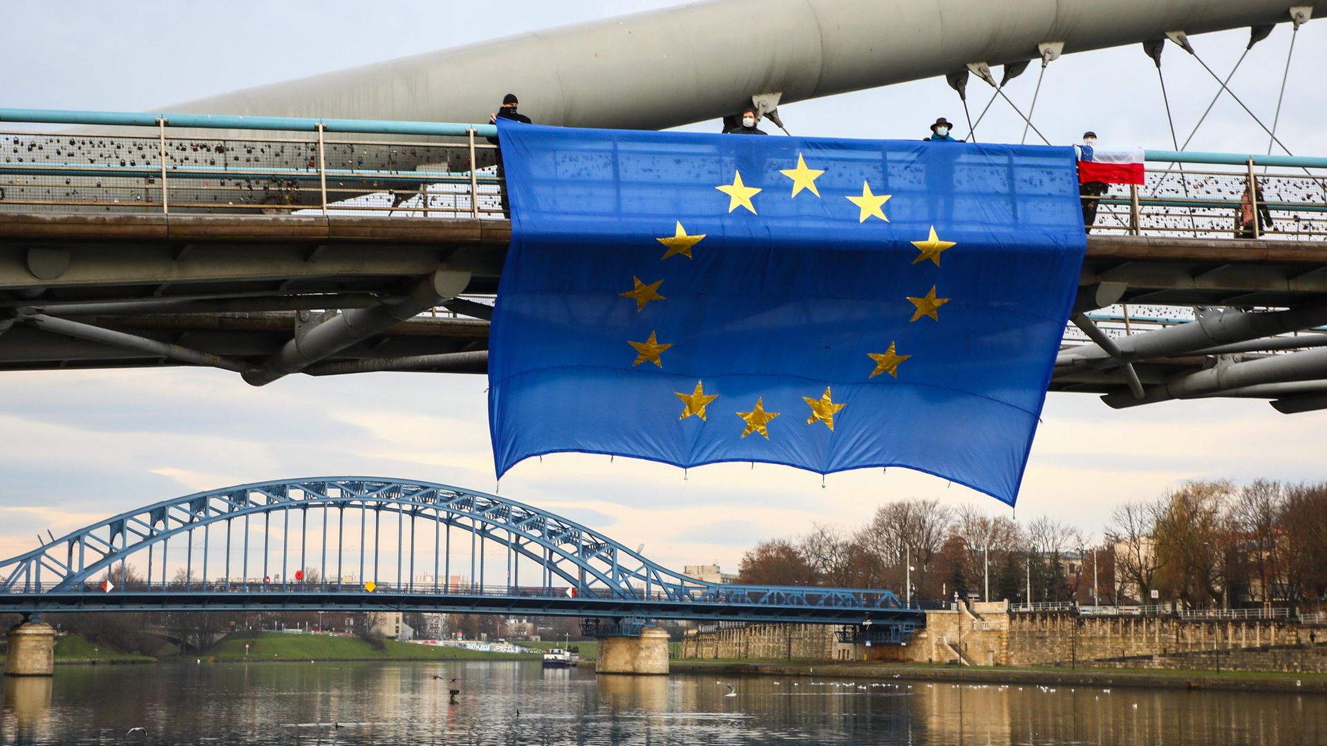 A huge EU flag hung on Father Bernatek footbridge over Vistula River, as part of an anti-government protest organised by the members of the Committee for the Defence of Democracy (KOD) in Krakow, Poland - Credit: NurPhoto via Getty Images