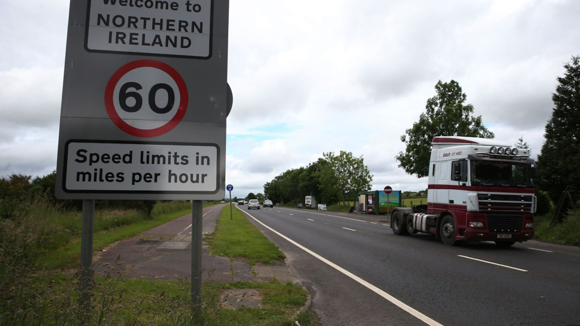 Traffic crossing the border between the Republic of Ireland and Northern Ireland in the village of Bridgend, Co Donegal - Credit: PA Wire/PA Images