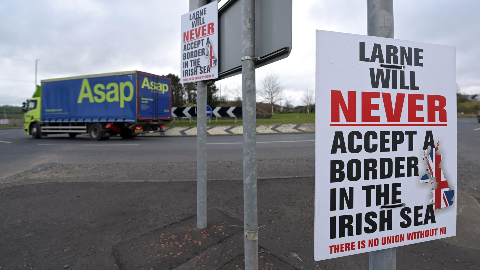 Freight arriving on the Cairnryan to Larne ferry passes a poster erected by Unionists against the Northern Ireland Protocol near Larne harbour - Credit: Getty Images
