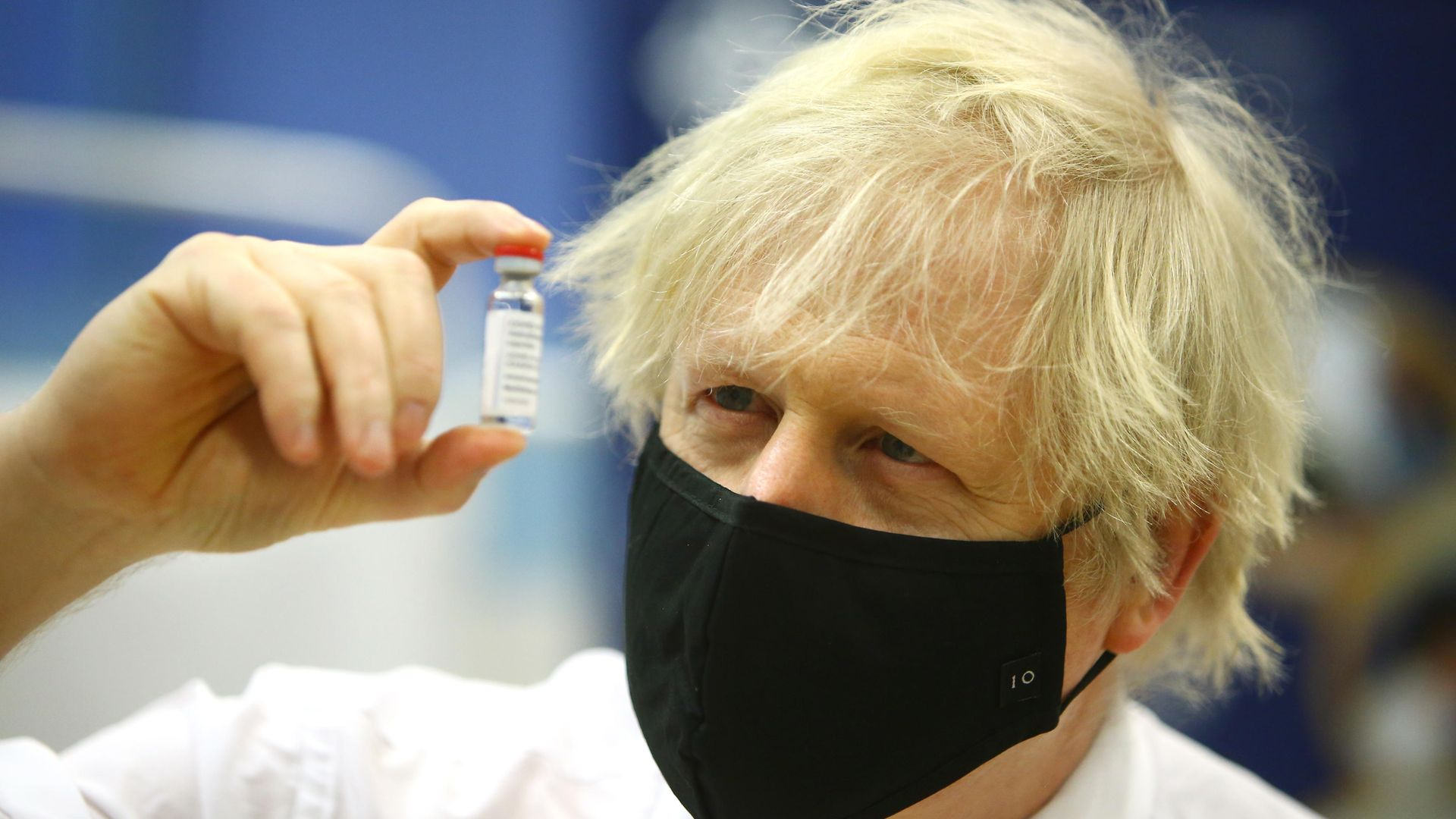 Prime minister Boris Johnson holding a vial of the Oxford/Astra Zeneca Covid-19 vaccine as he visits a vaccination centre at Cwmbran Stadium in Cwmbran, south Wales. Picture date: Wednesday February 17, 2021. - Credit: PA