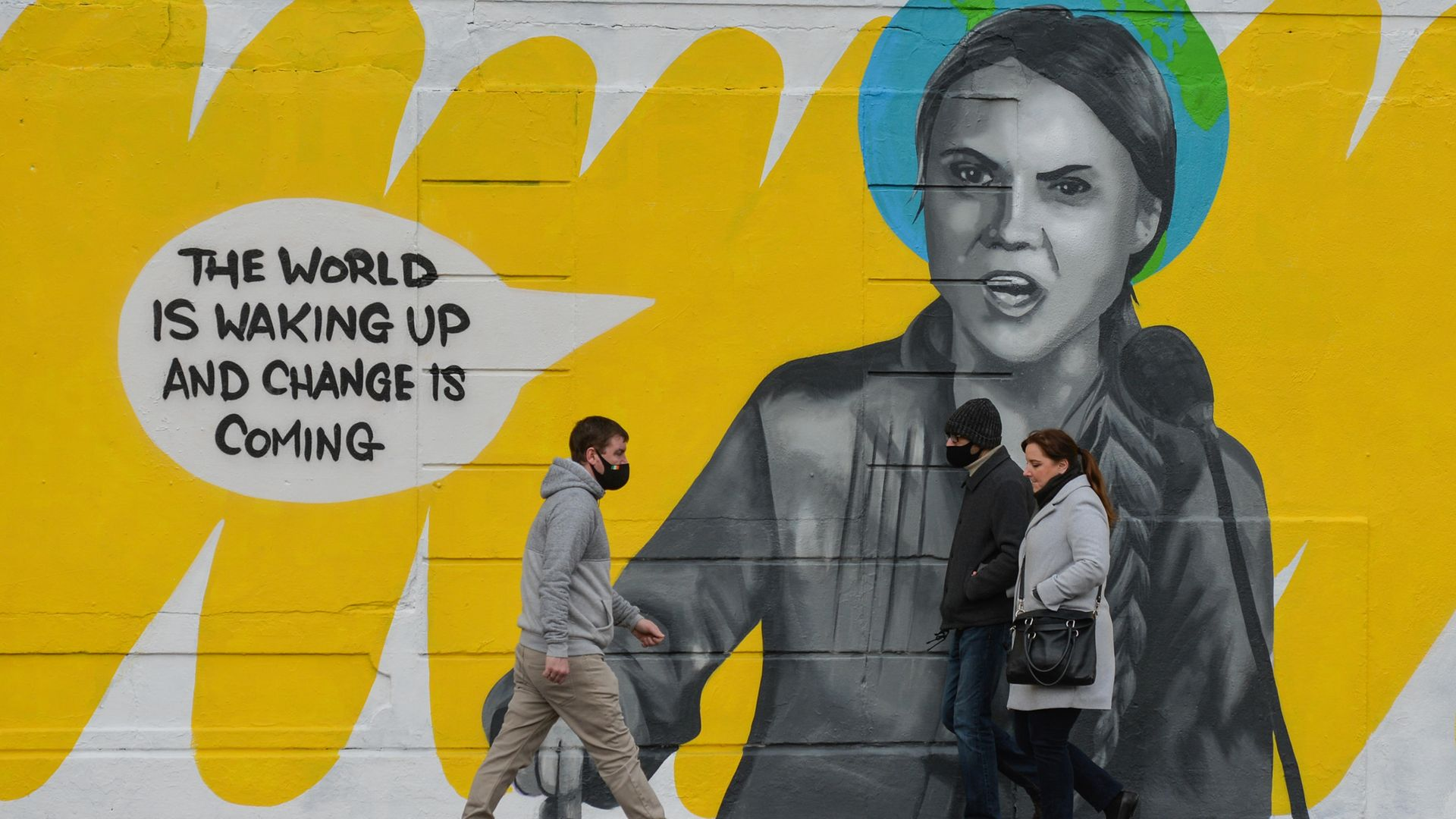 People walk by a mural in Dublin city centre of Swedish environmental activist Greta Thunberg - Credit: NurPhoto via Getty Images