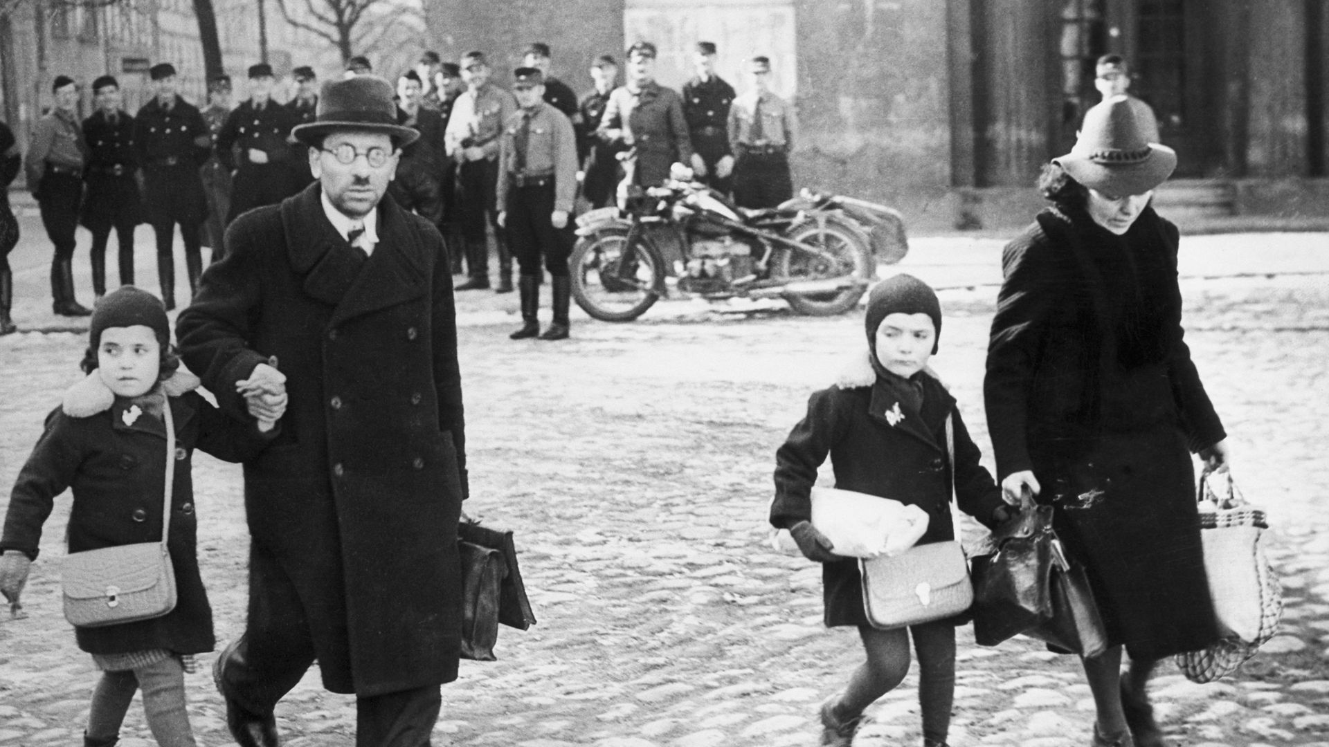 Uniformed Nazis watch a family of refugee Jews fleeing from Memel – now Klaipėda – after it was occupied by Germany in 1939, Adolf Hitler's last territorial acquisition before the war - Credit: Bettmann Archive