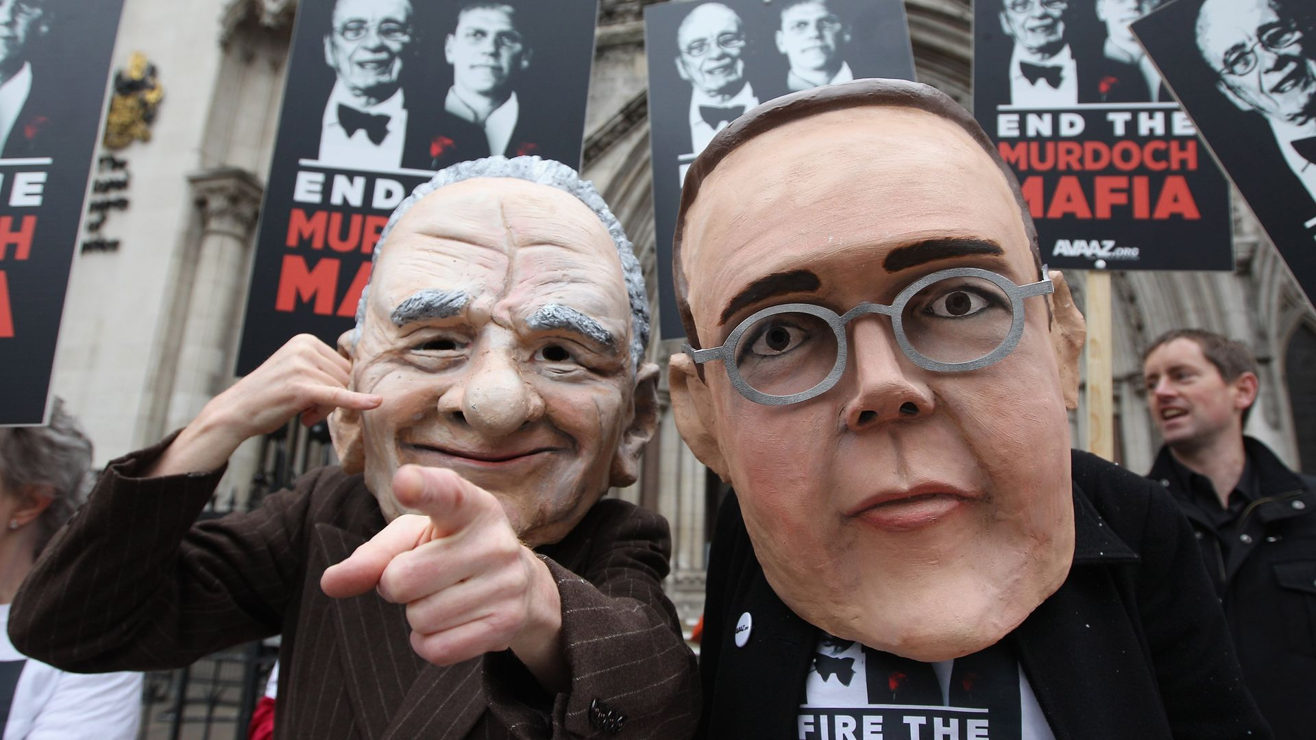 Protesters from the campaign group 'Avaaz' demonstrate outside the High Court with large James and Rupert Murdoch masks - Credit: Getty Images
