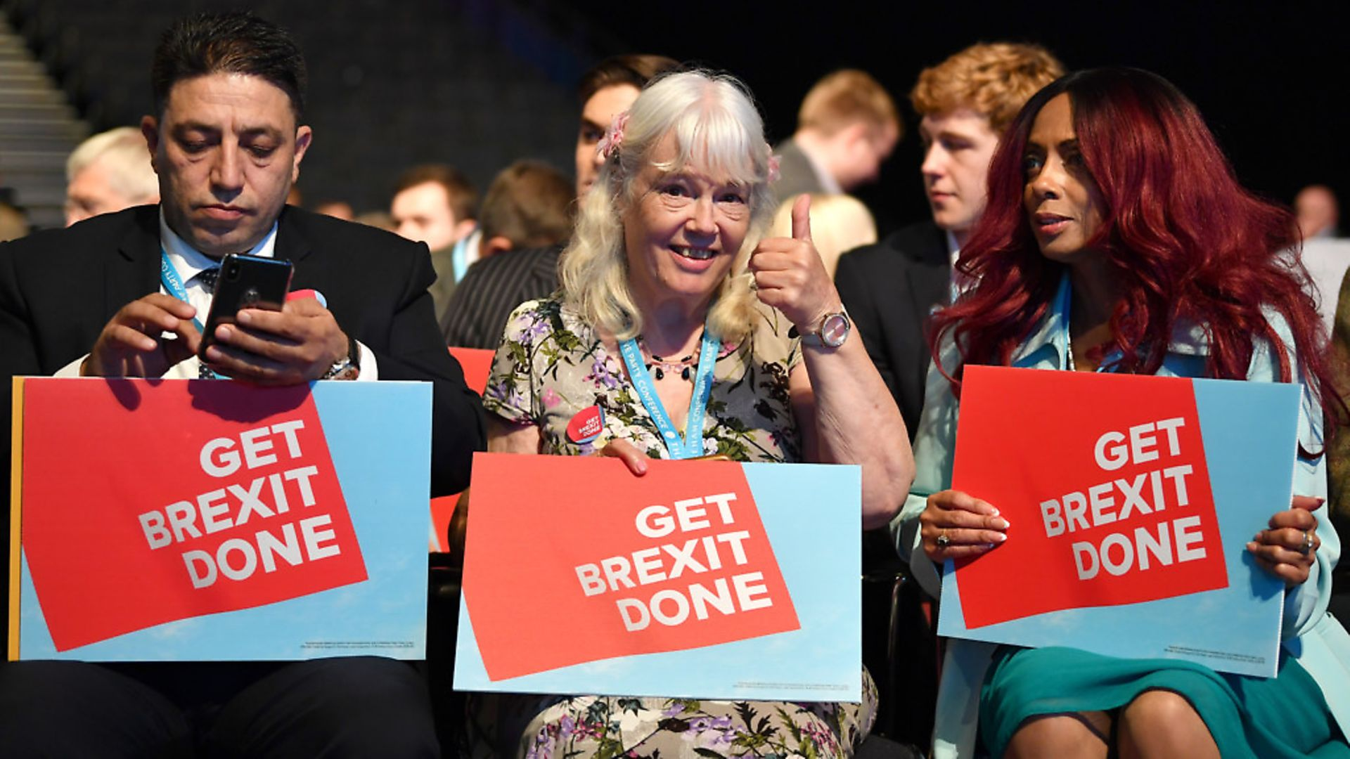 """Delegates hold """"Get Brexit Done"""" posters during the first day of Conservative Party Conference 2019. (Photo by Jeff J Mitchell/Getty Images) - Credit: Getty Images"""