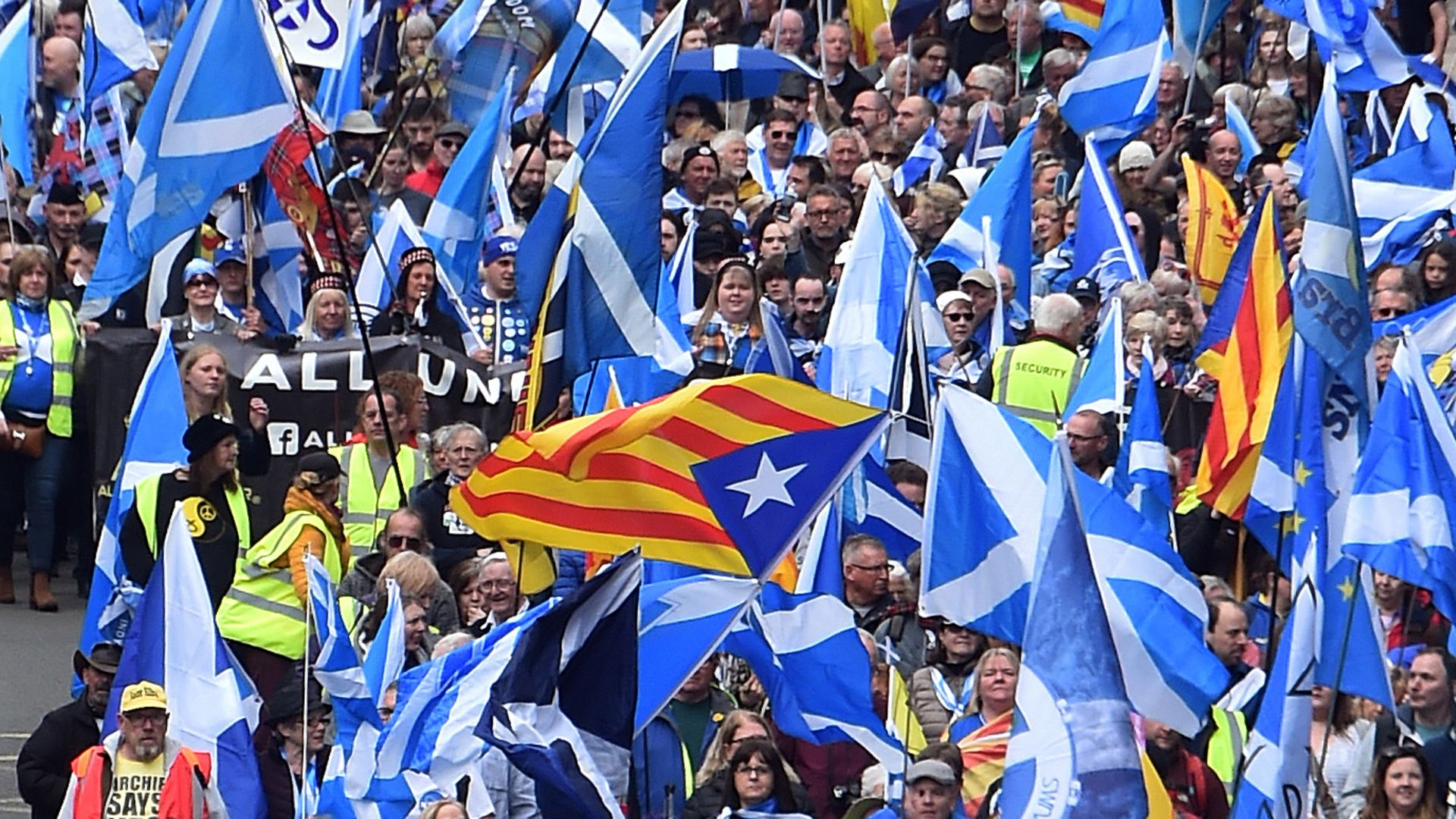 Catalan Estelada flags fly alongside Saltires at a pro-Scottish independence march in Glasgow in May, 2019 - Credit: AFP via Getty Images