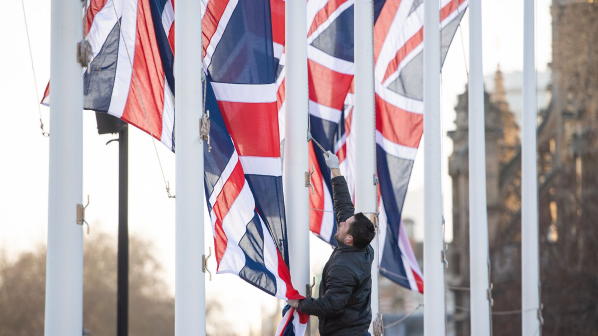 A worker removes Union flags from flagpoles in Parliament Square, London - Credit: PA