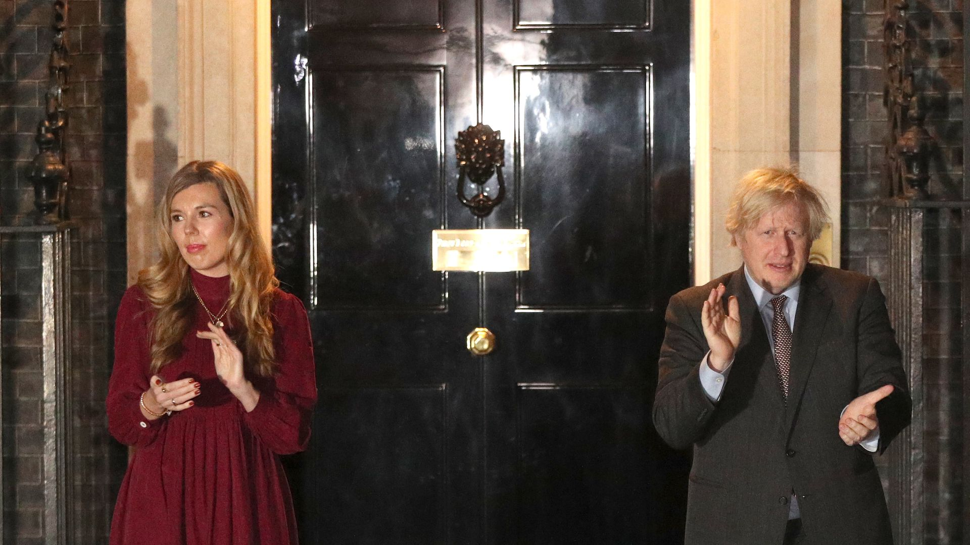 Prime minister Boris Johnson and his partner Carrie Symonds outside 10 Downing Street, London, join in with a nationwide clap in honour of Captain Sir Tom Moore - Credit: PA