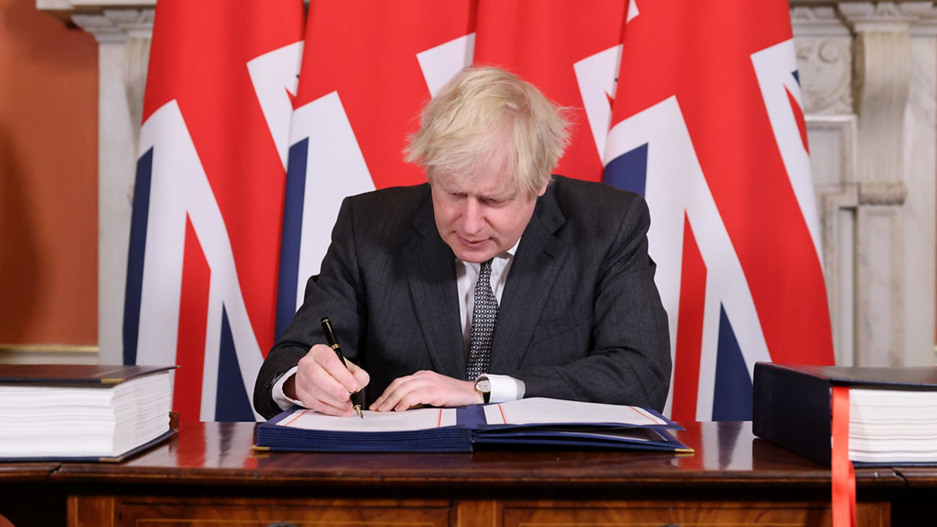 Boris Johnson signs the Brexit agreement - Credit: Andrew Parsons / No10 Downing St