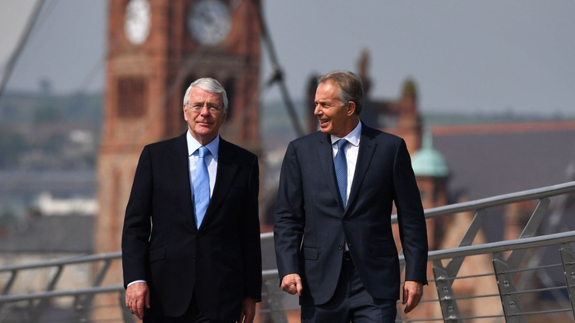 Former prime ministers Sir John Major (left) and Tony Blair walk across the Peace Bridge in Londonderry - Credit: PA Archive/PA Images