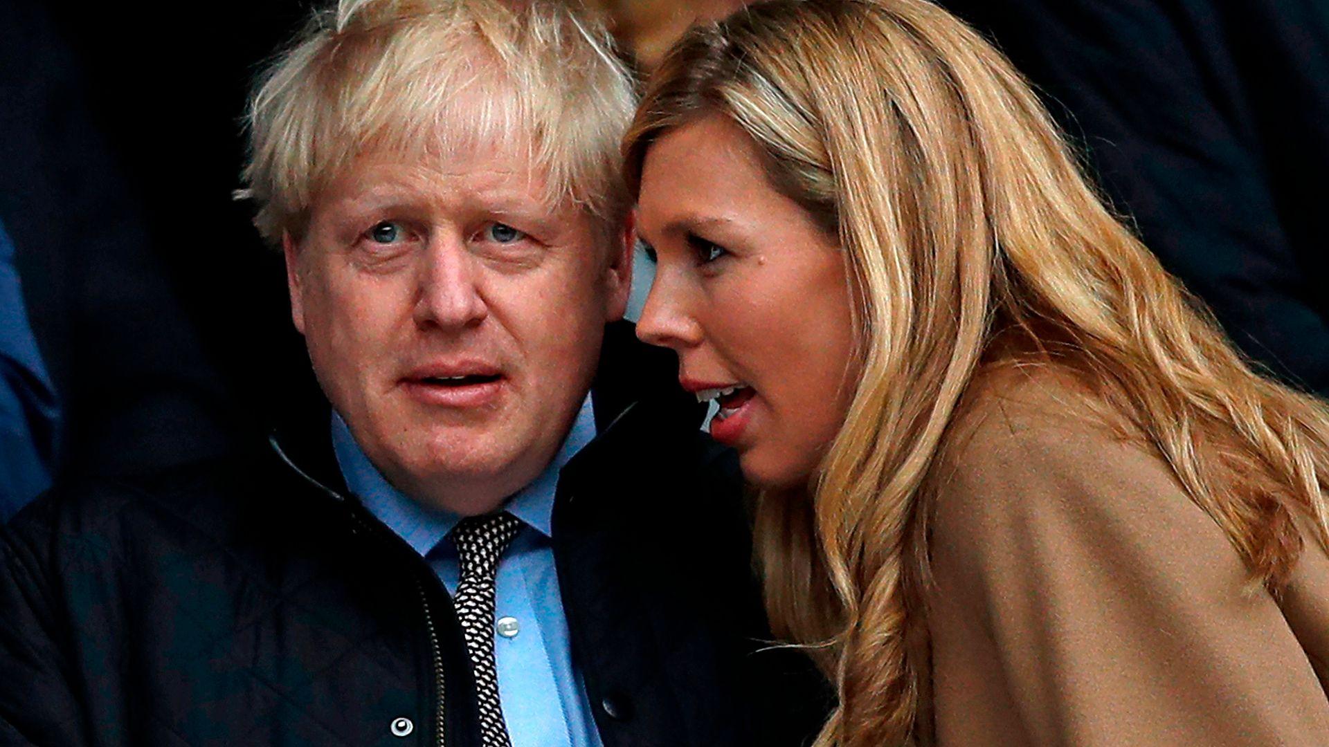 Boris Johnson with his partner Carrie Symonds (R) - Credit: AFP via Getty Images