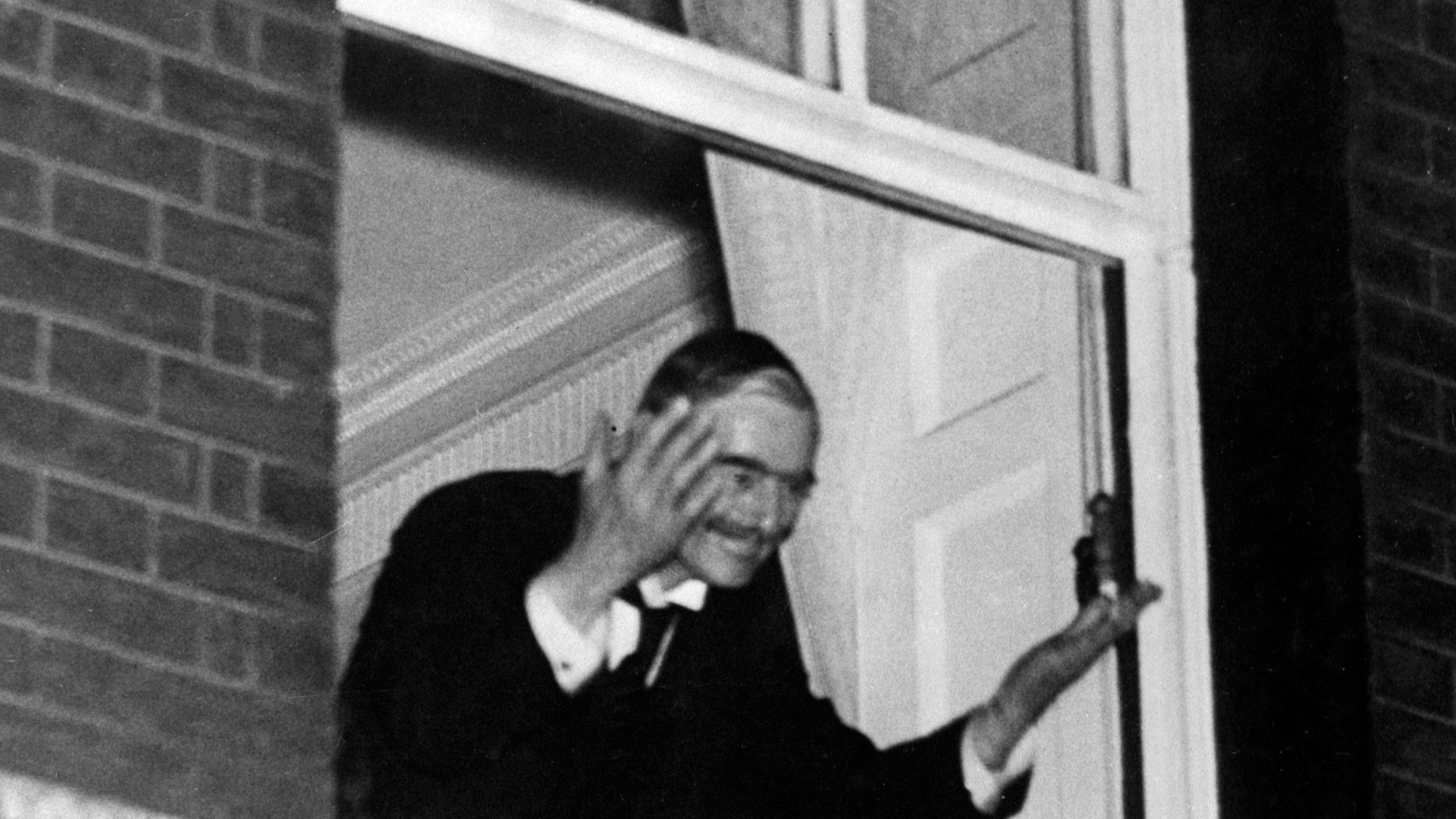Neville Chamberlain waves to crowds from the window of No.10 after the Munich Agreement was signed. - Credit: PA