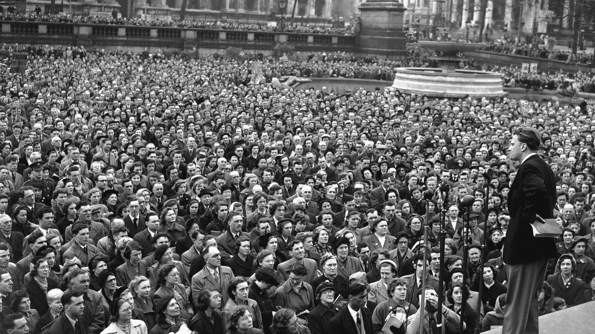 Bible in hand, American evangelist Billy Graham speaks to a crowd in Trafalgar Square in 1954 - Credit: Bettmann Archive