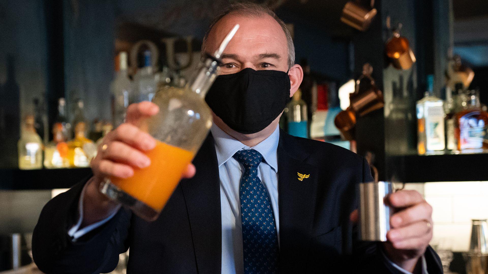 Liberal Democrats leader Sir Ed Davey tries his hand at cocktail making during a visit to Bar Bodega in Watford - Credit: PA