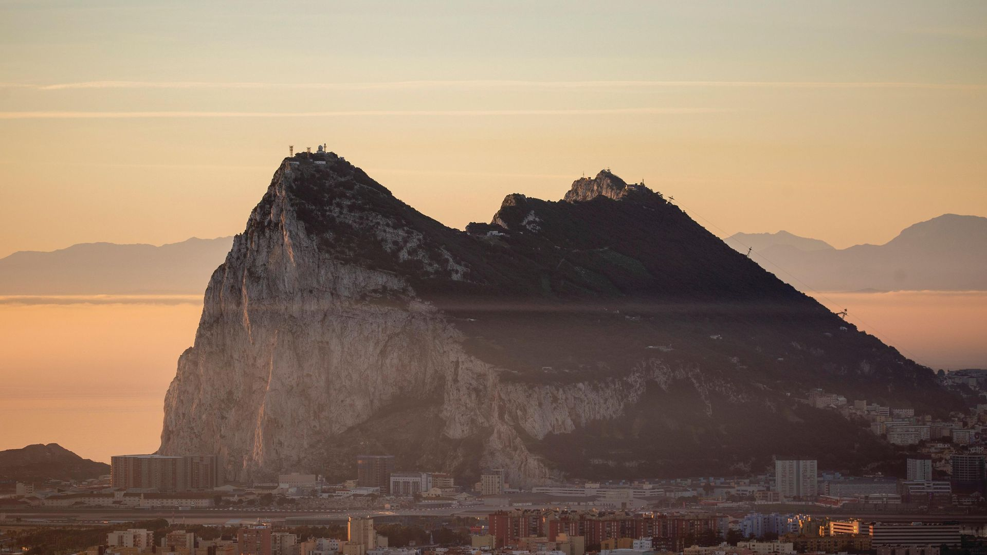 The Gibraltar Rock is seen at sunrise from the Spanish side - Credit: Getty Images