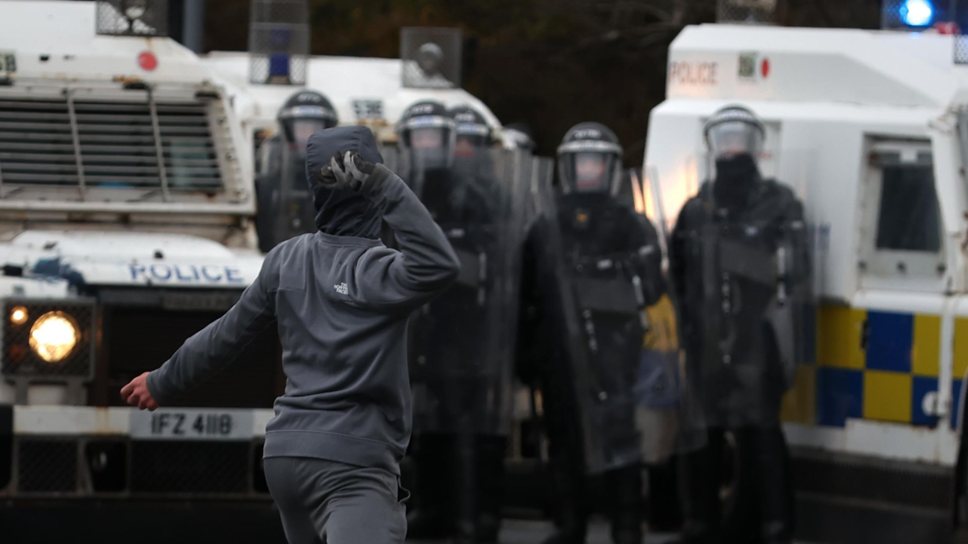 Youths throw stones towards PSNI officers on the Springfield road, during further unrest in Belfast - Credit: PA