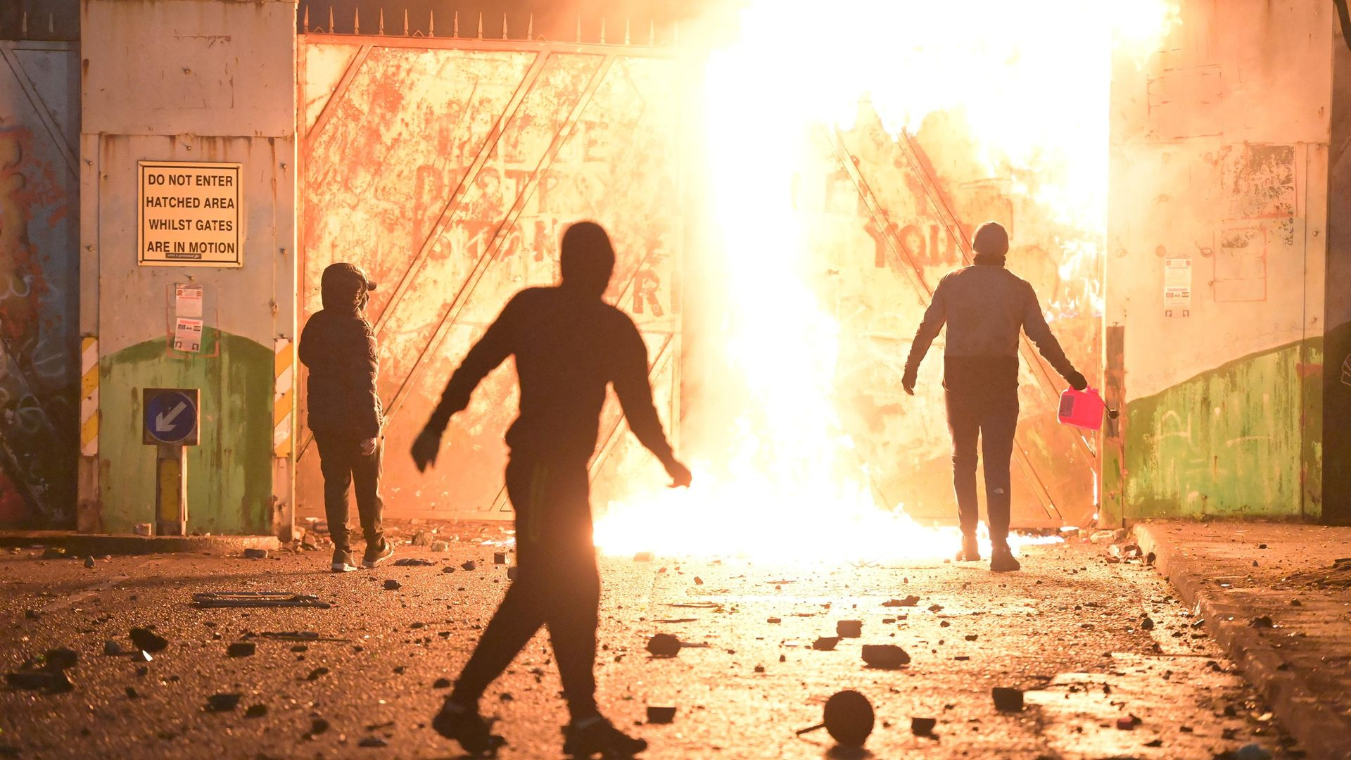 VIOLENCE AT THE PEACE GATE: Fire fed by petrol burns as youths clash with police at Belfast's Springfield road/Lanark Way interface in early April - Credit: Charles McQuillan/Getty Images