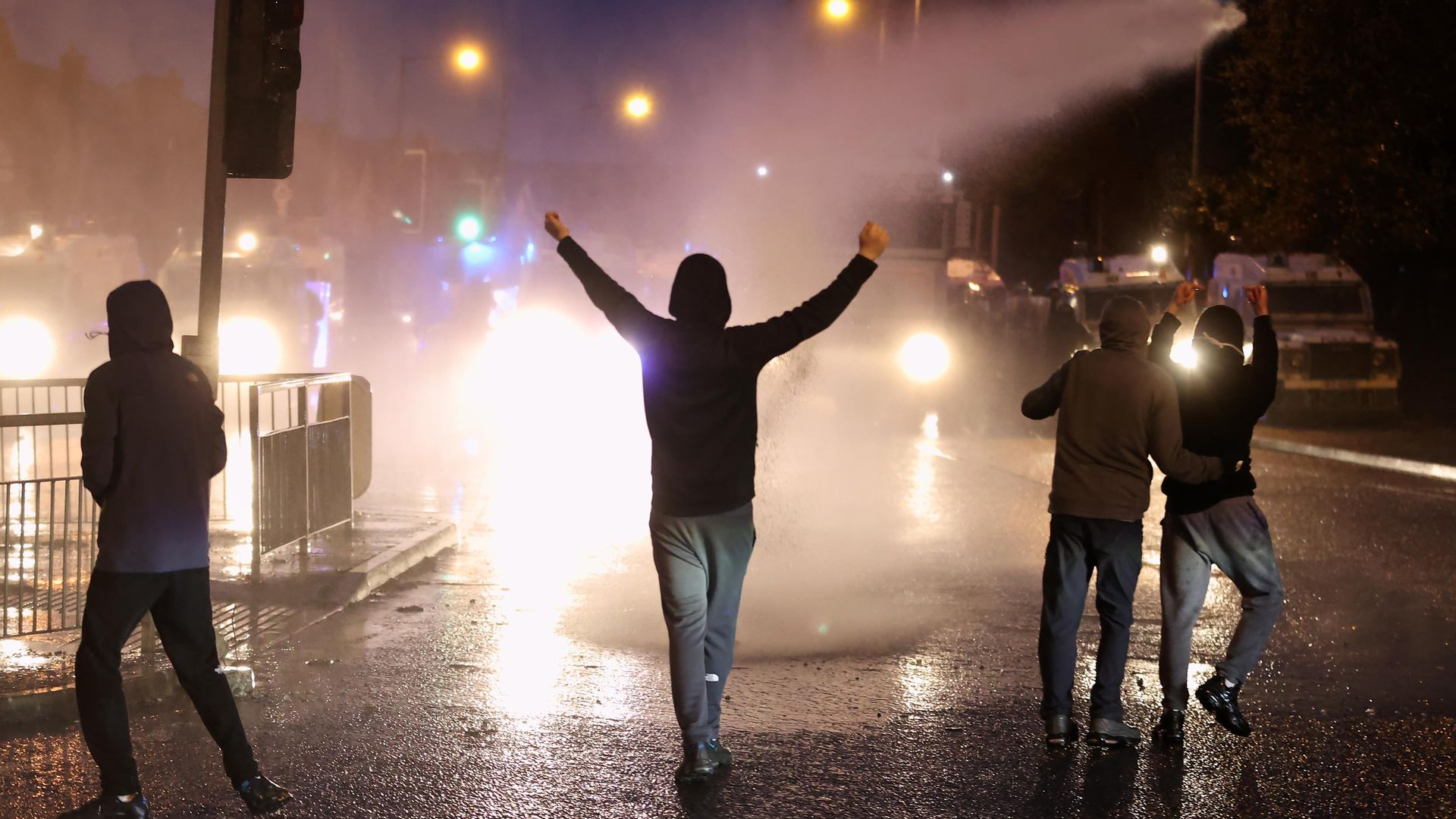 The PSNI use a water cannon on youths on the Springfield road, during further unrest in Belfast - Credit: PA