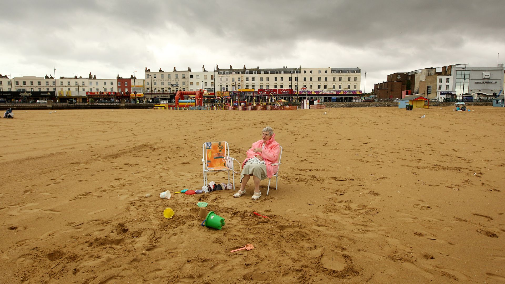 A beachgoer sits in a deckchair below grey clouds in Margate - Credit: Getty Images