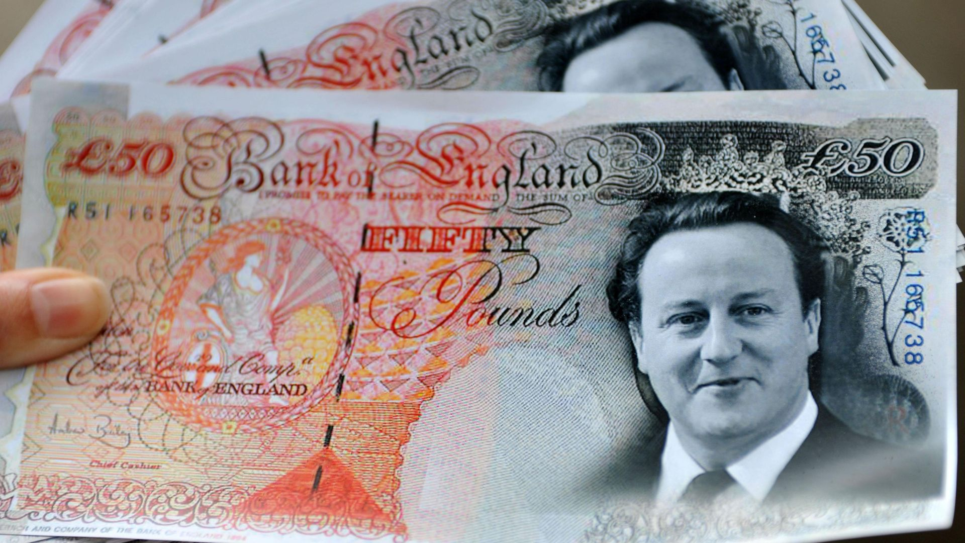 Mock £50 notes featuring the head of David Cameron, held by members of the union UNISON demonstrating his proposals for the NHS in 2011 - Credit: PA