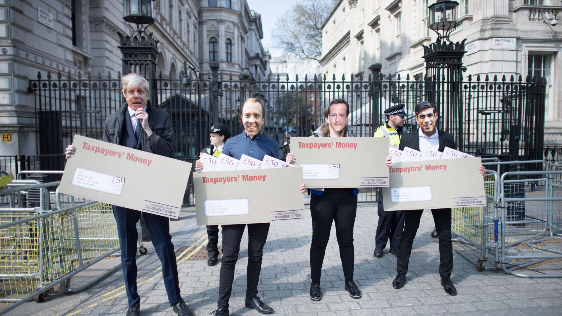 Labour activists wearing face masks, depicting prime minister Boris Johnson, chancellor Rishi Sunak, health secretary Matt Hancock and former PM David Cameron - Credit: PA