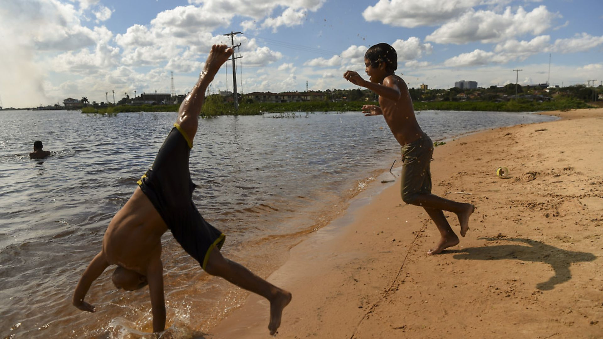 Children play by the shore of the Paraguay river in Asuncion. Photo: EITAN ABRAMOVICH/AFP via Getty Images - Credit: AFP via Getty Images